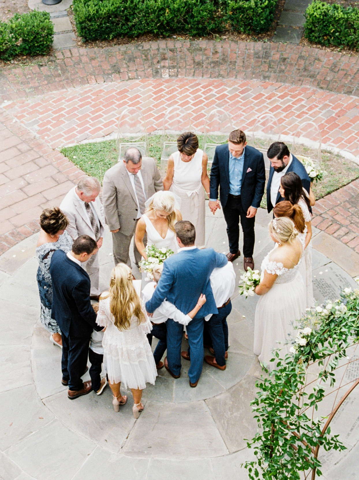 bride and groom surrounded by family in prayer circle