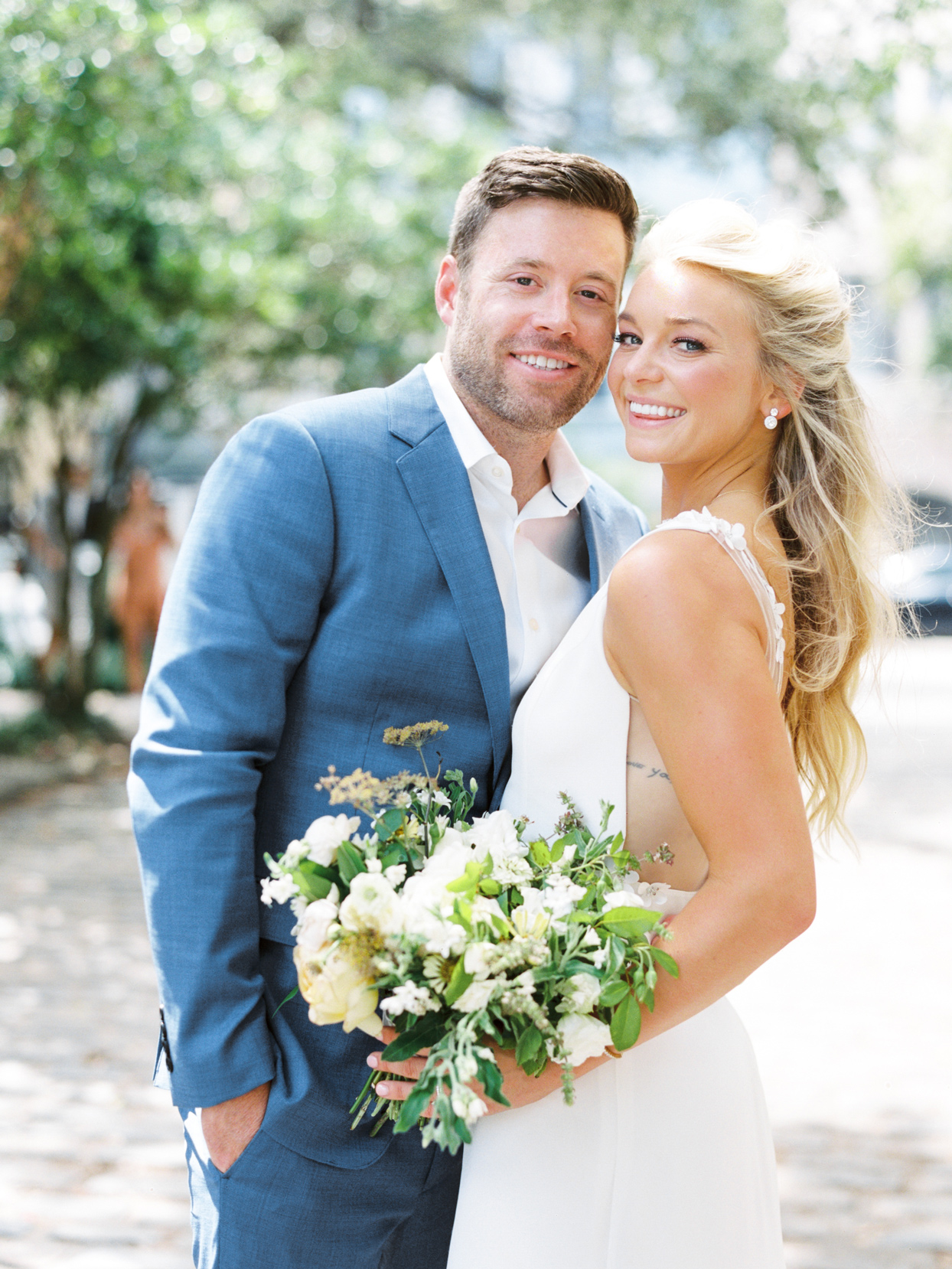 bride holding bouquet with groom smiling