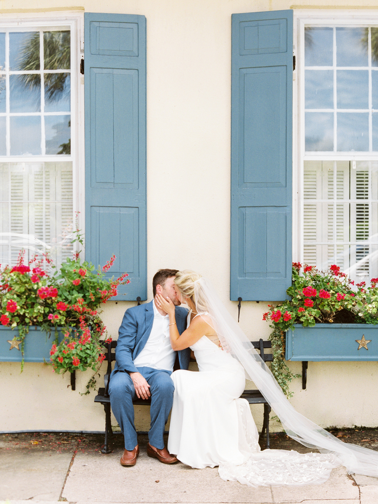 bride and groom share a kiss sitting on a bench