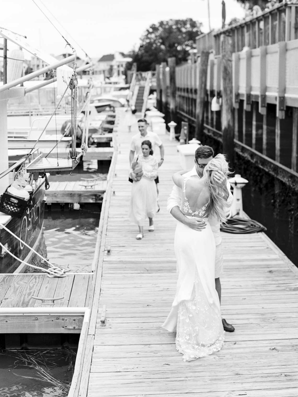 bride and groom share a kiss standing on boat dock