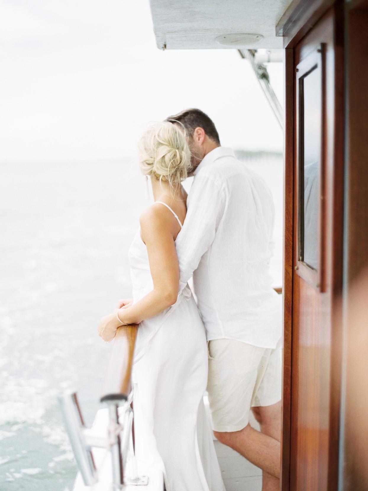 bride and groom standing on boat overlooking water
