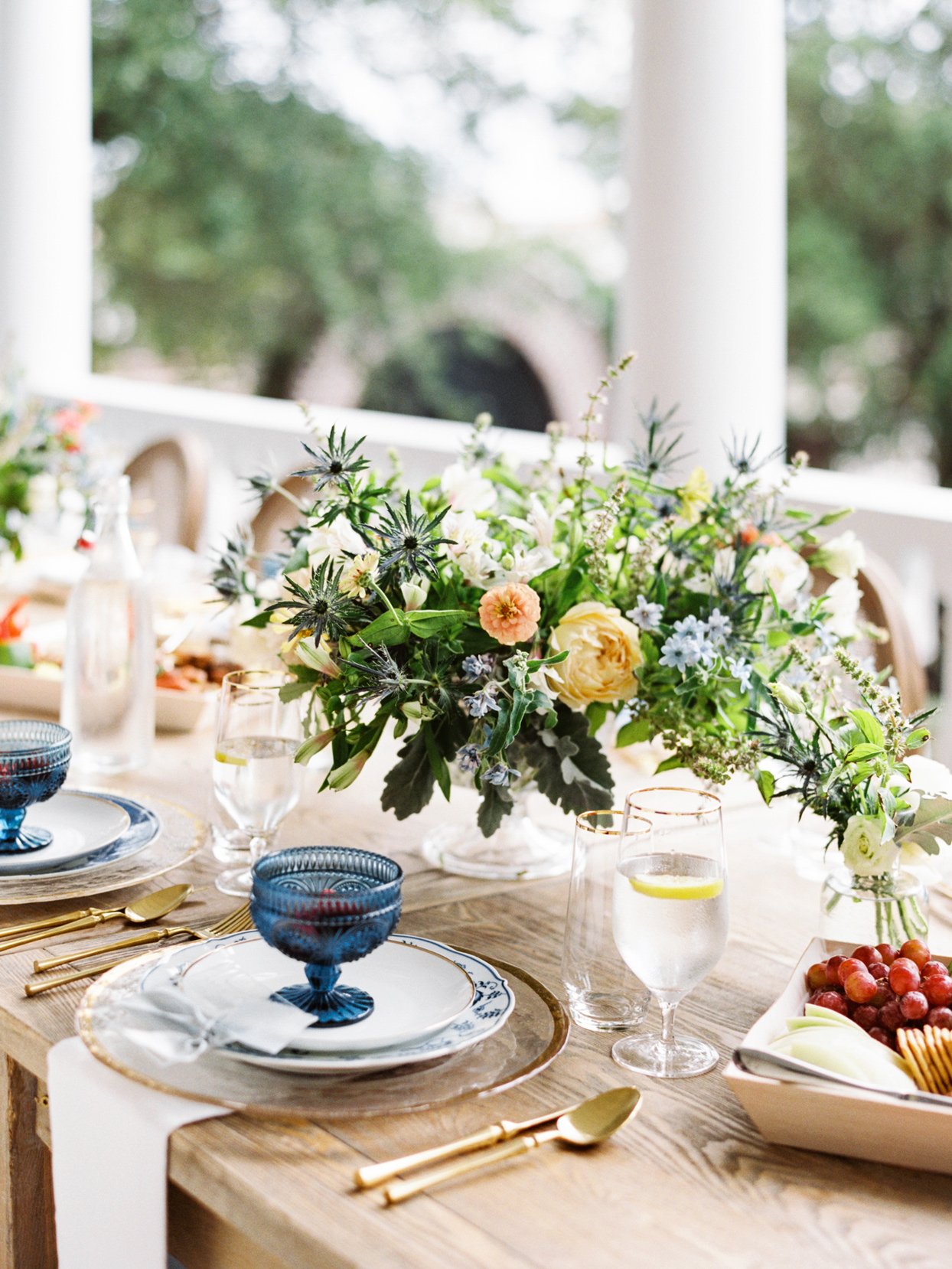 gold and blue place settings with floral centerpieces