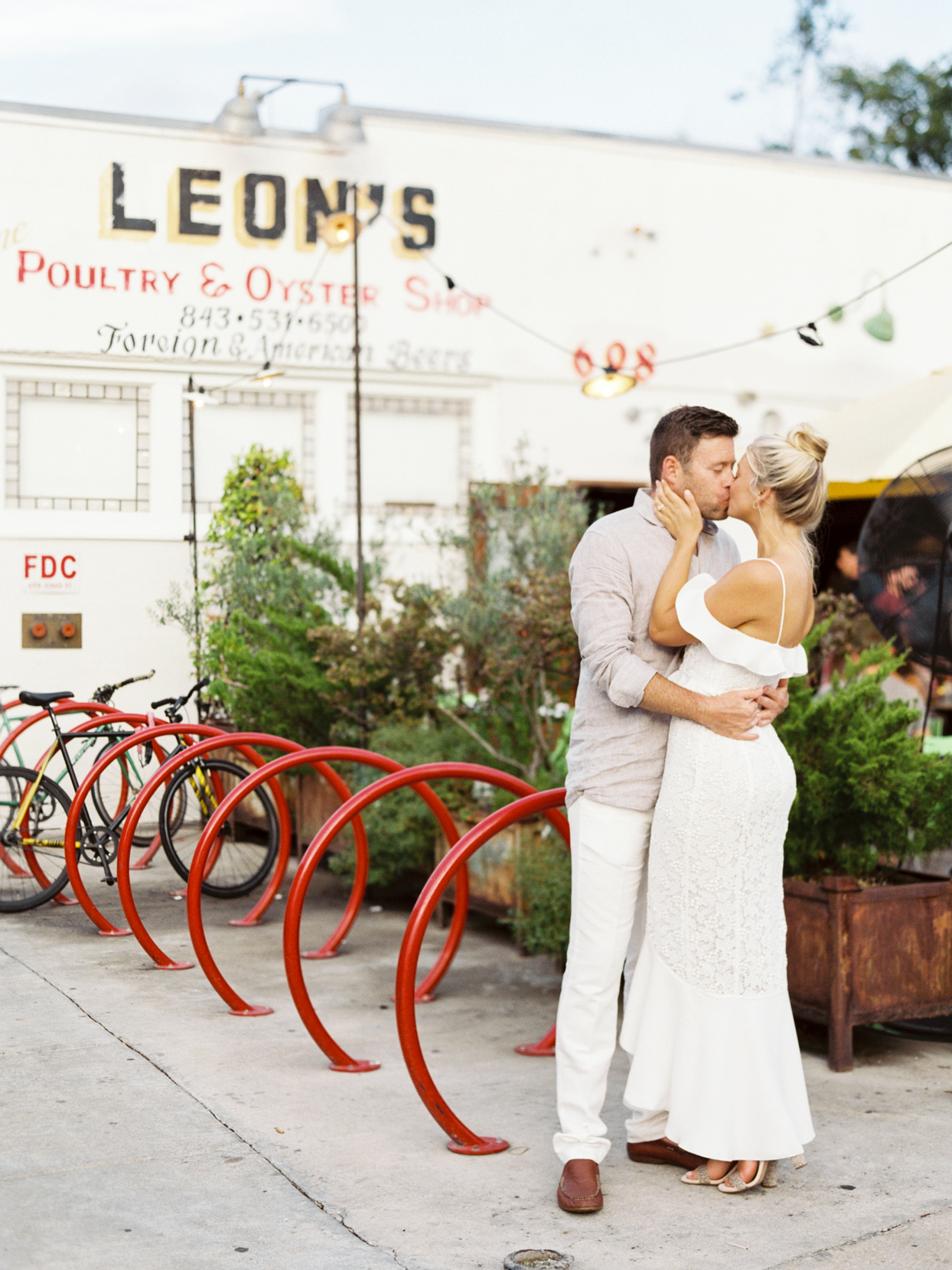 bride and groom share kiss outside rehearsal dinner venue