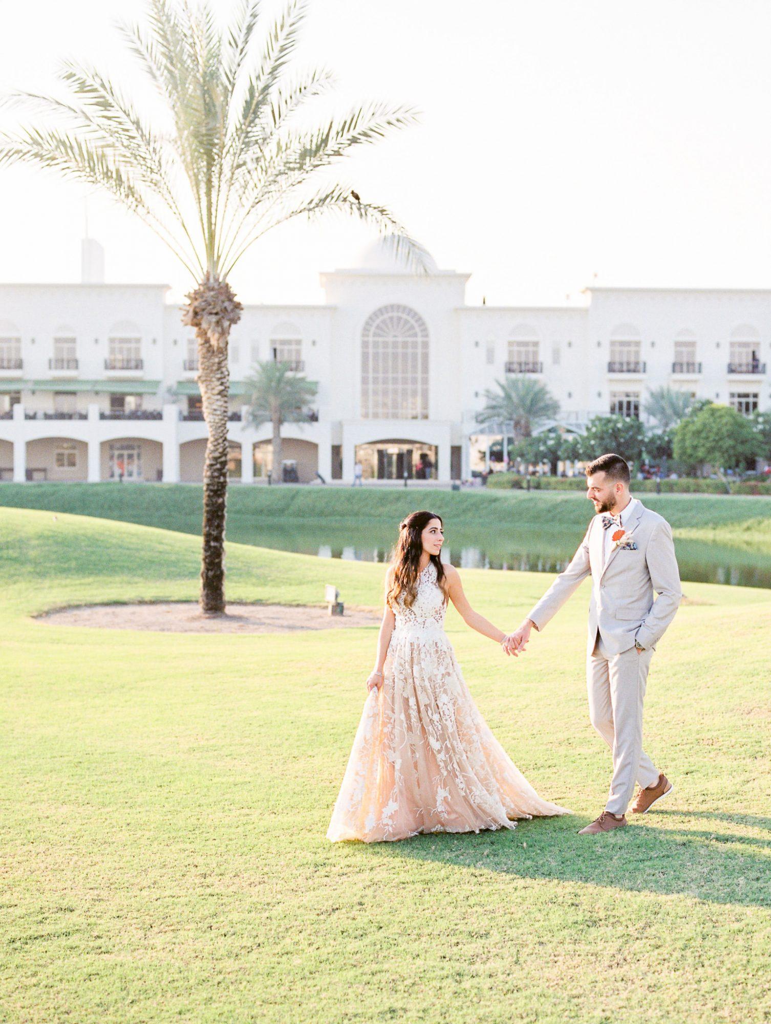 wedding couple walking hand-in-hand across lawn
