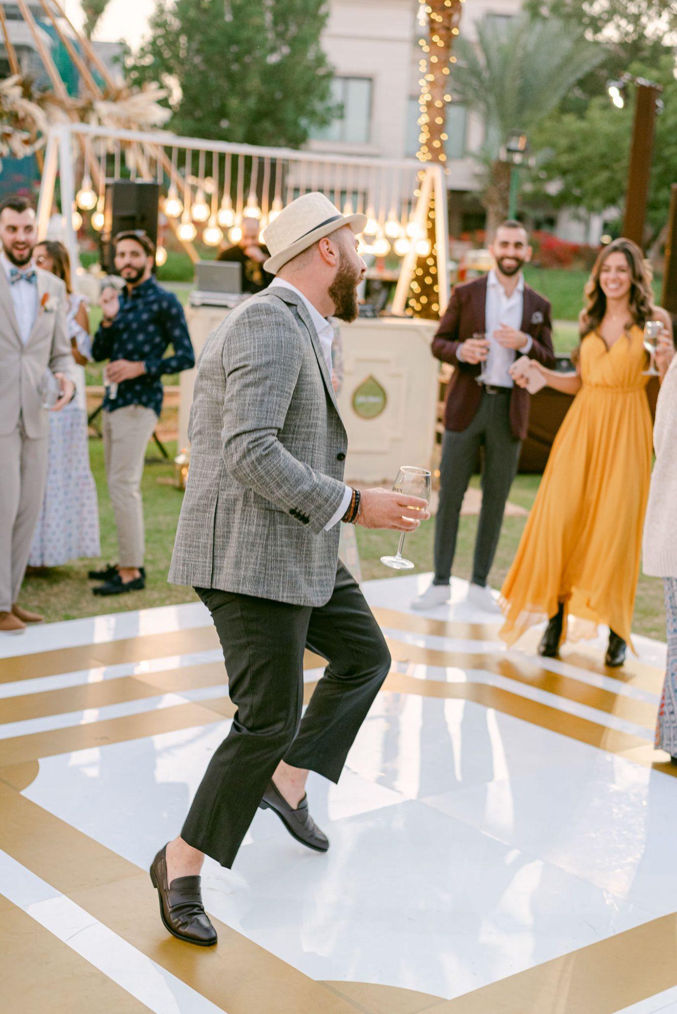 guest dancing on outdoor dance floor with drink