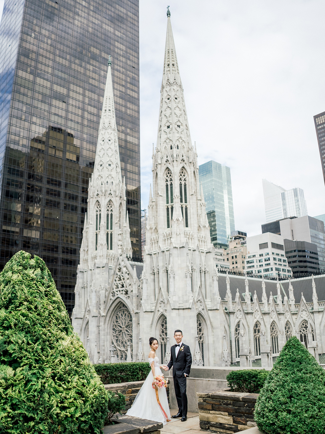 wedding couple posing on rooftop in front of cathedral