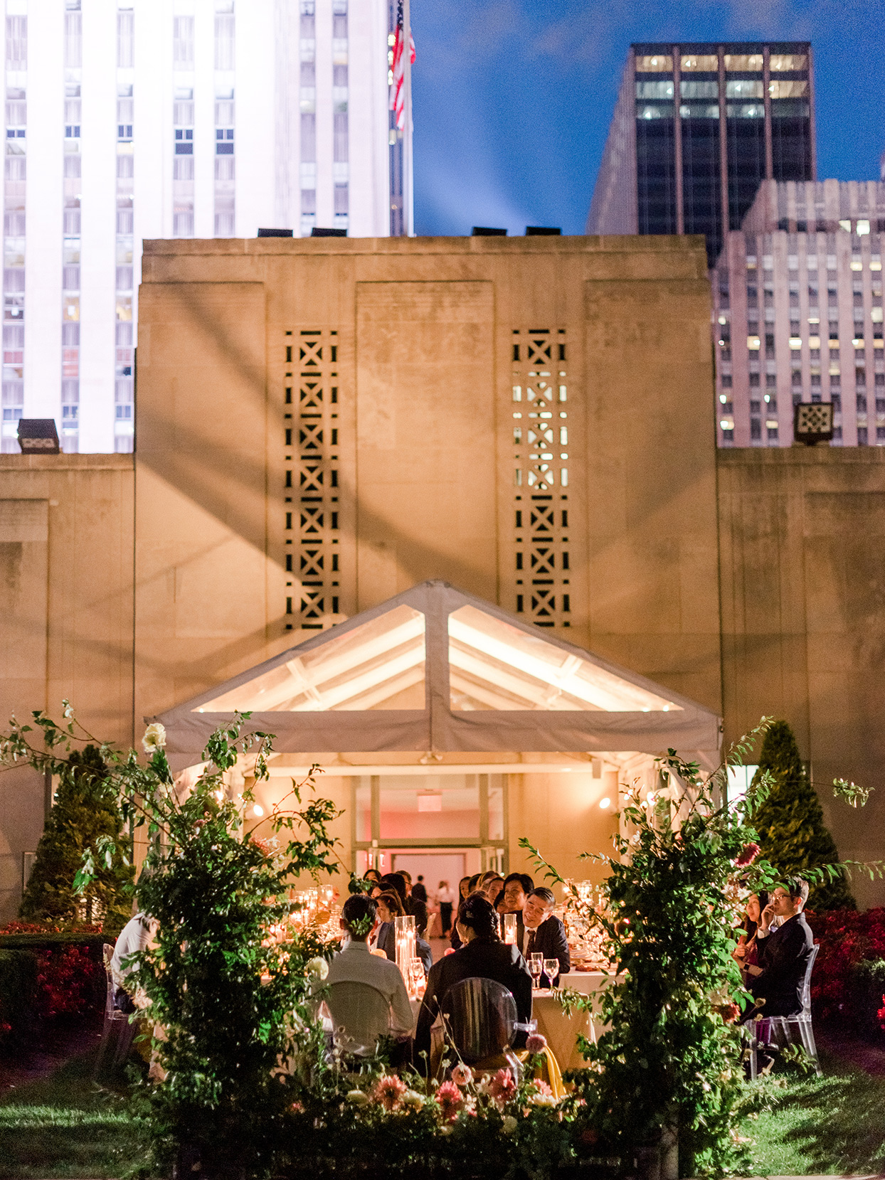 guests sitting under tent during night time dinner at round tables