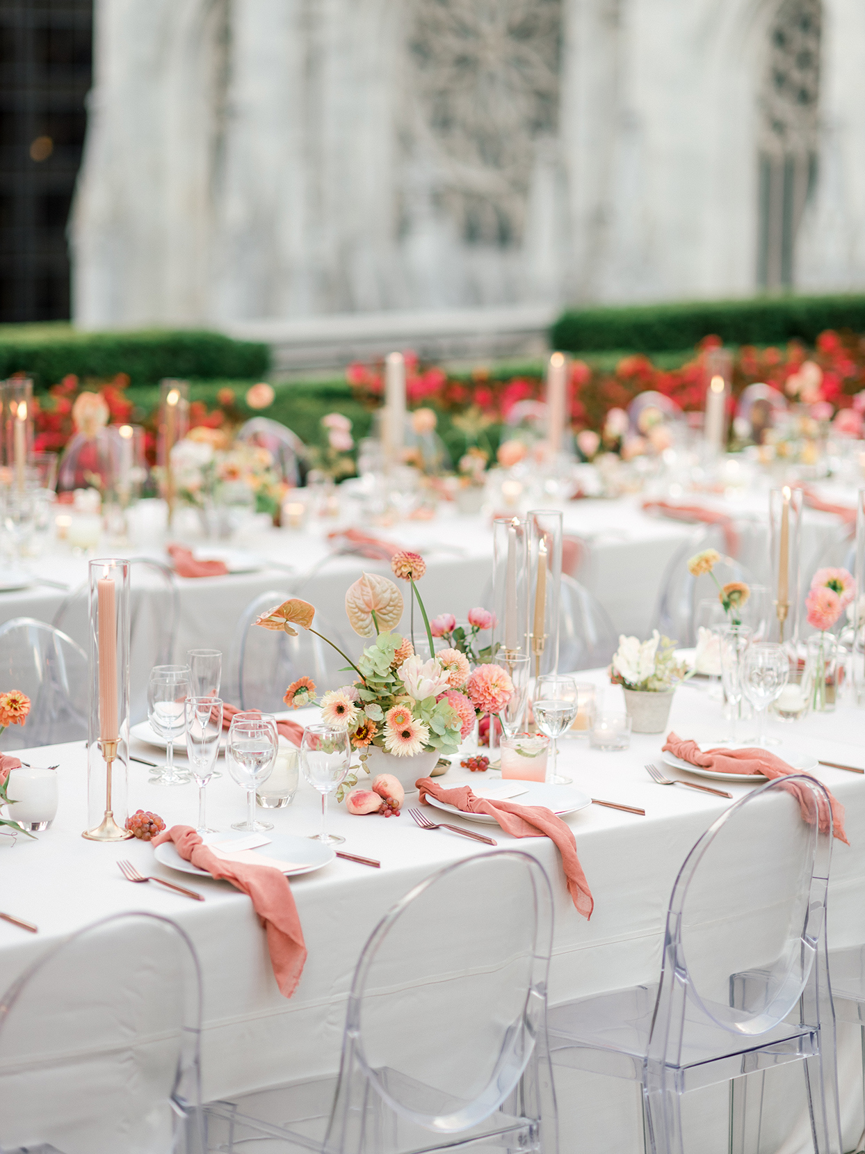 wedding reception white tables with peach and coral decorations and clear chairs