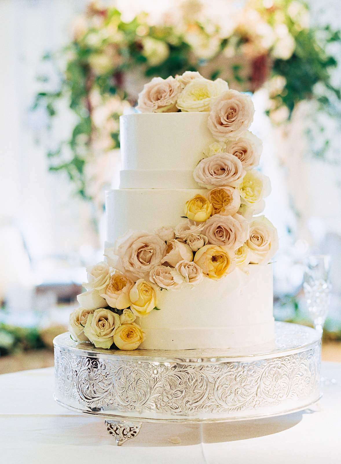 three-tier wedding cake decorated with garland of fresh flowers
