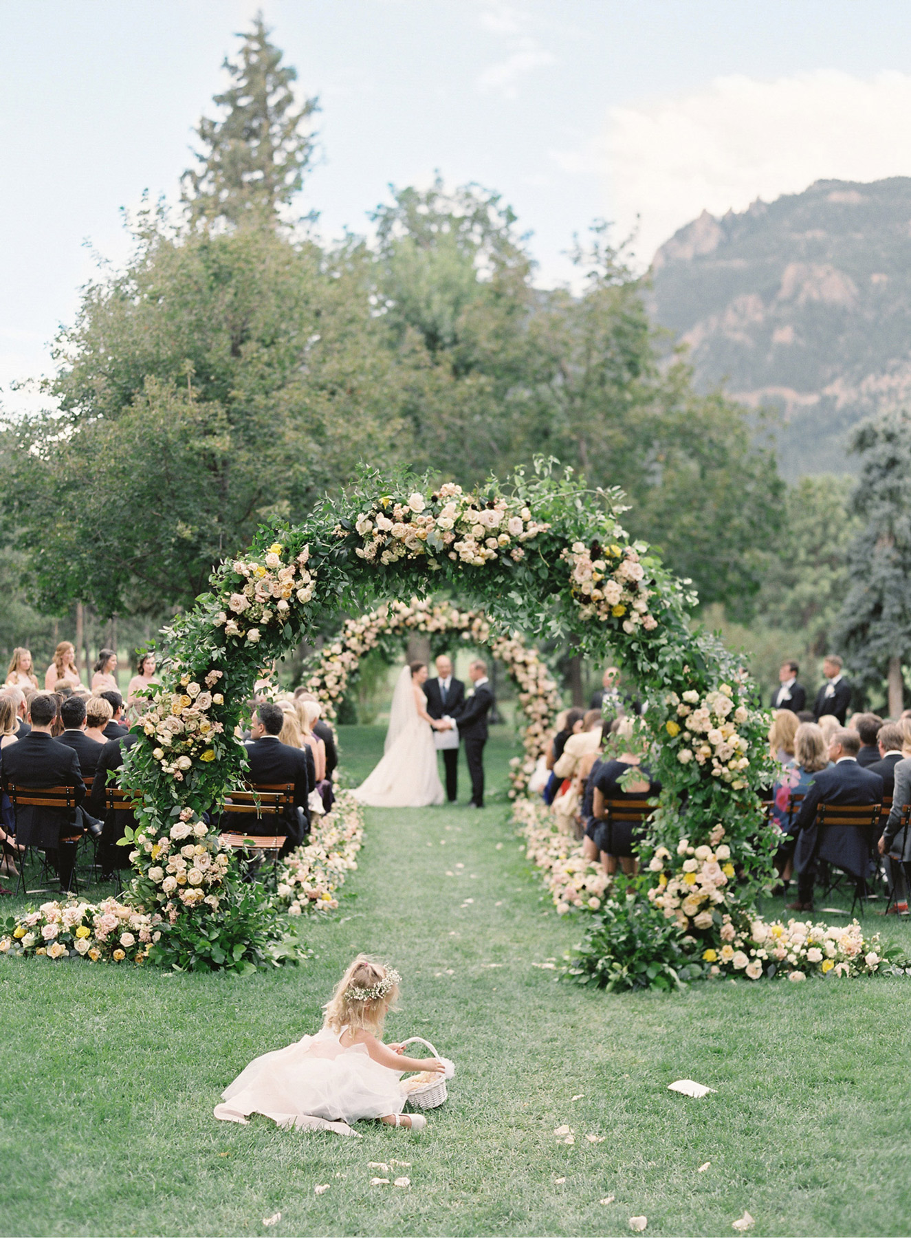 flower girl sitting in grass with flower petals in forefront of arches during ceremony