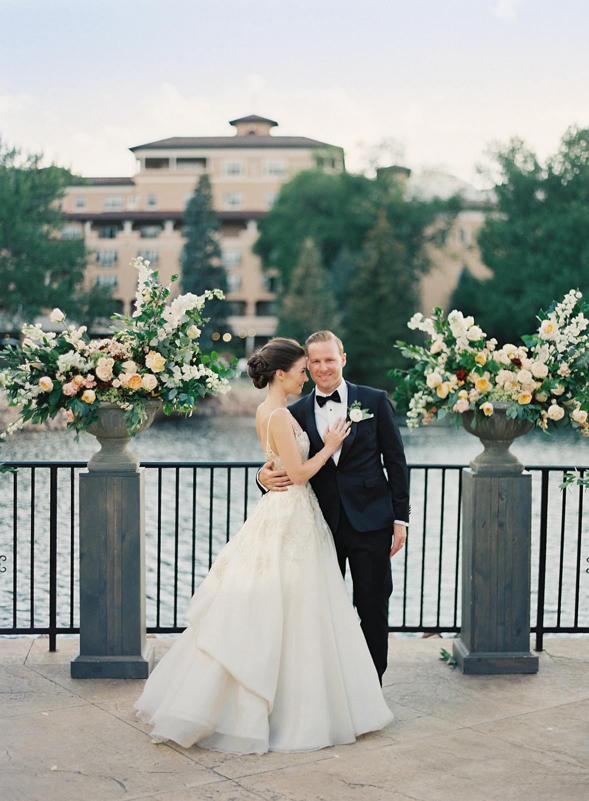 bride and groom outdoor terrace between floral urns