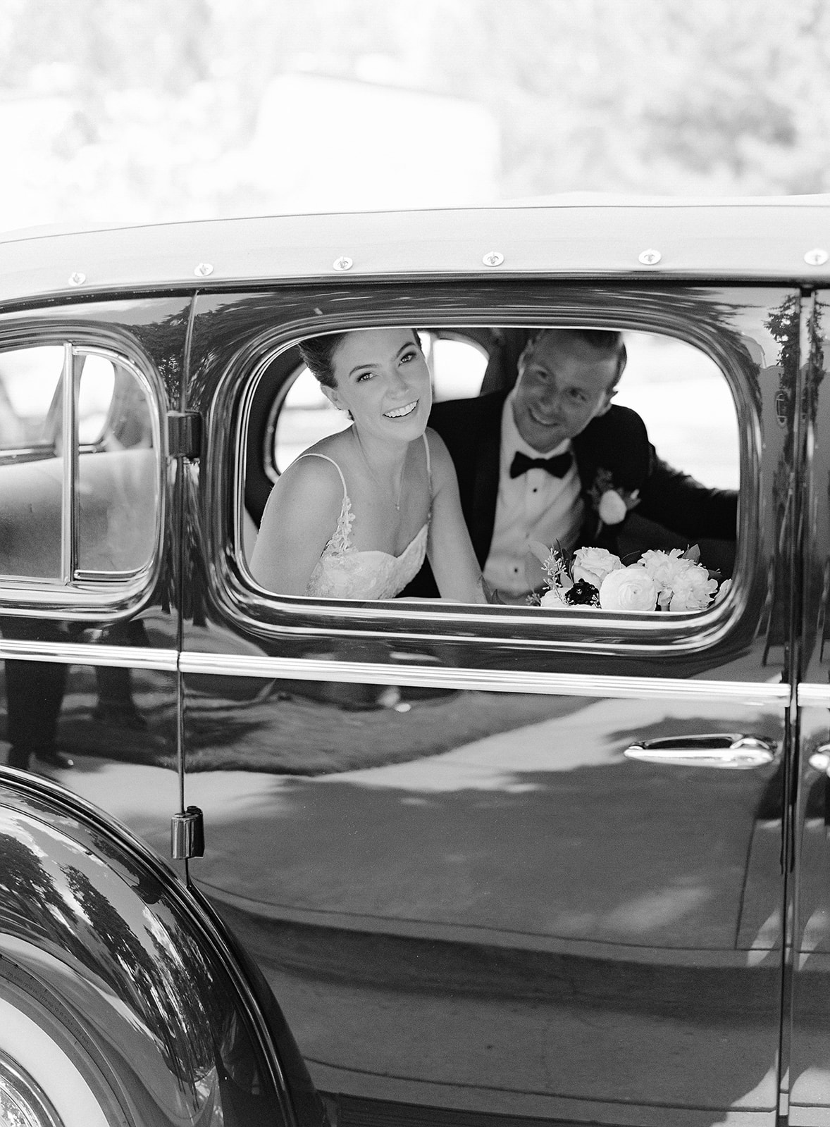 black and white photo of bride and groom in wedding car