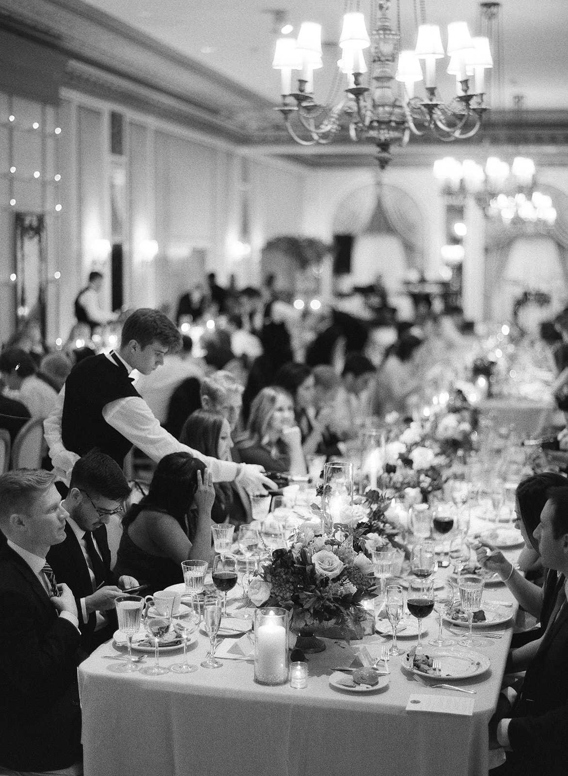 black and white photo guests at long banquet tables during dinner
