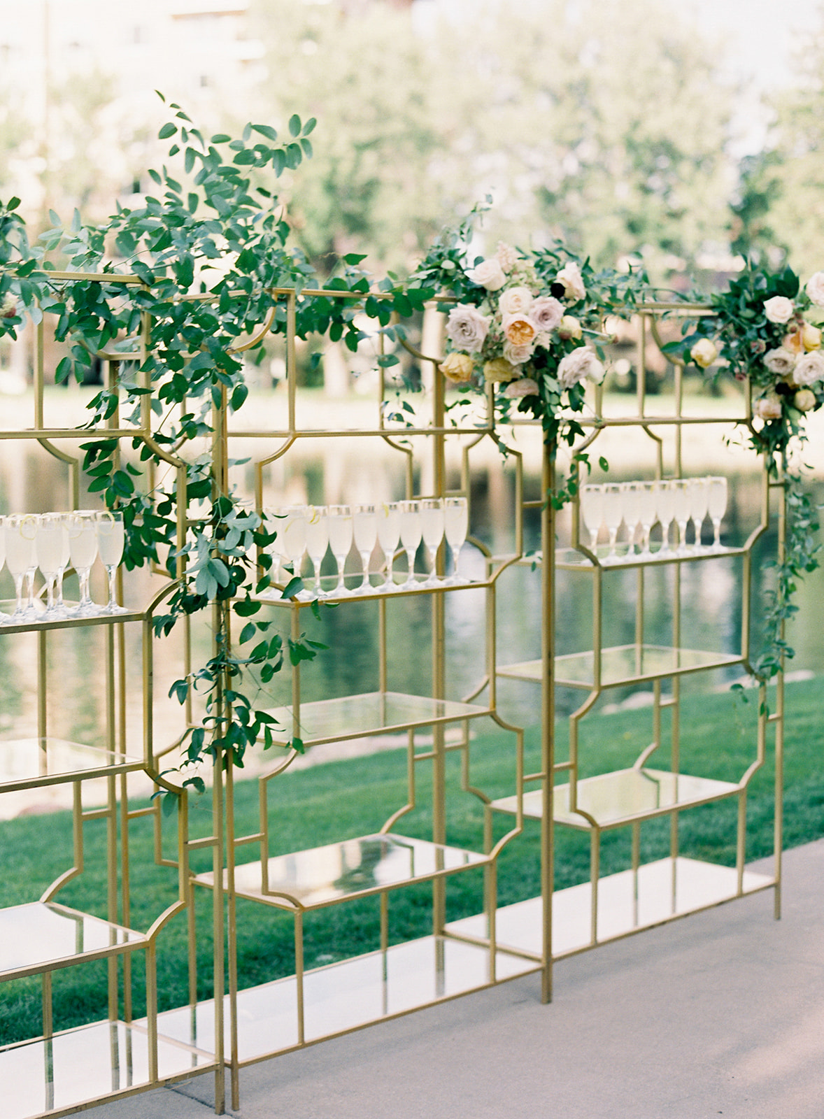 drinks on glass shelves decorated with greenery and flowers