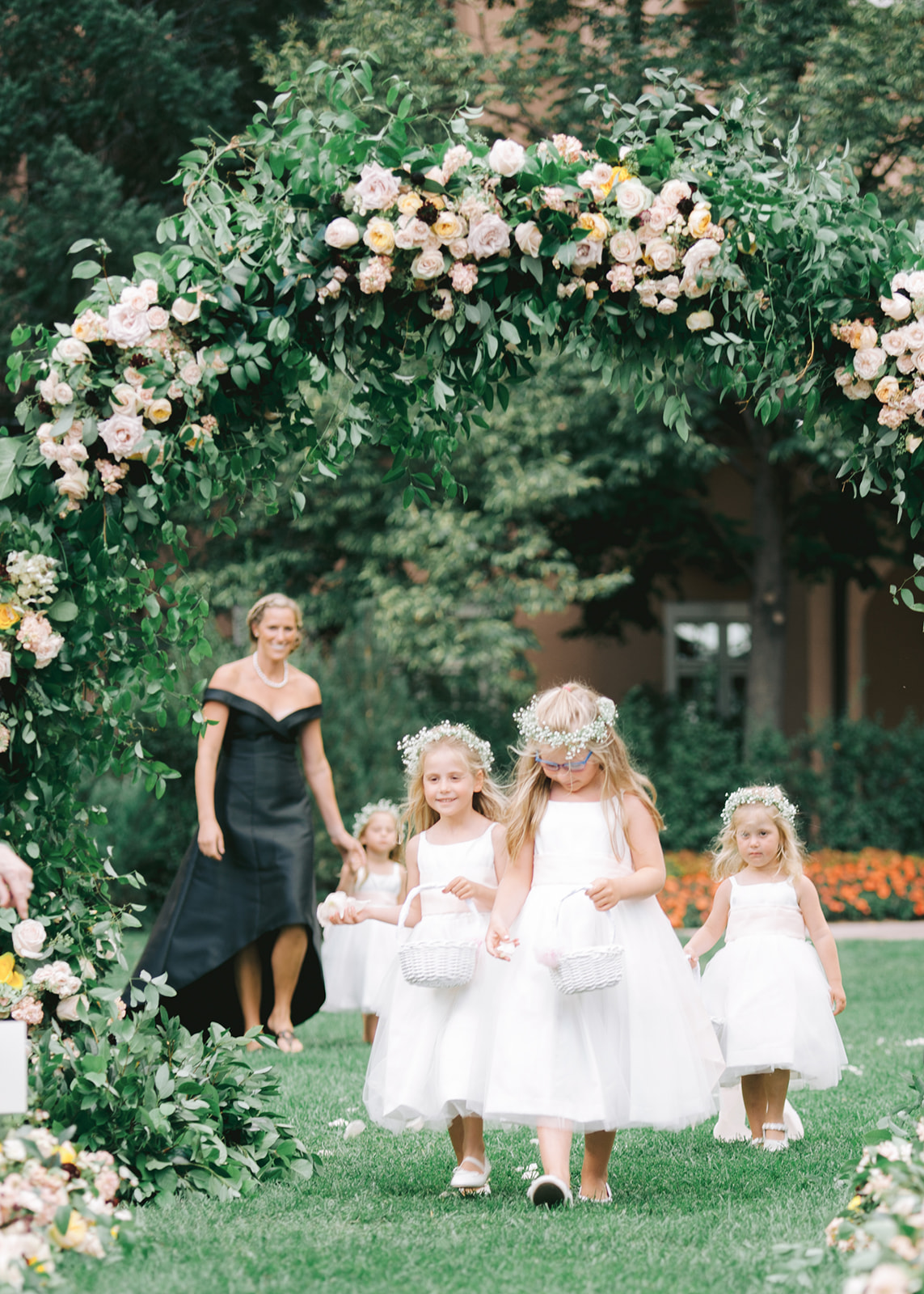 four flower girls walking down aisle throwing petals