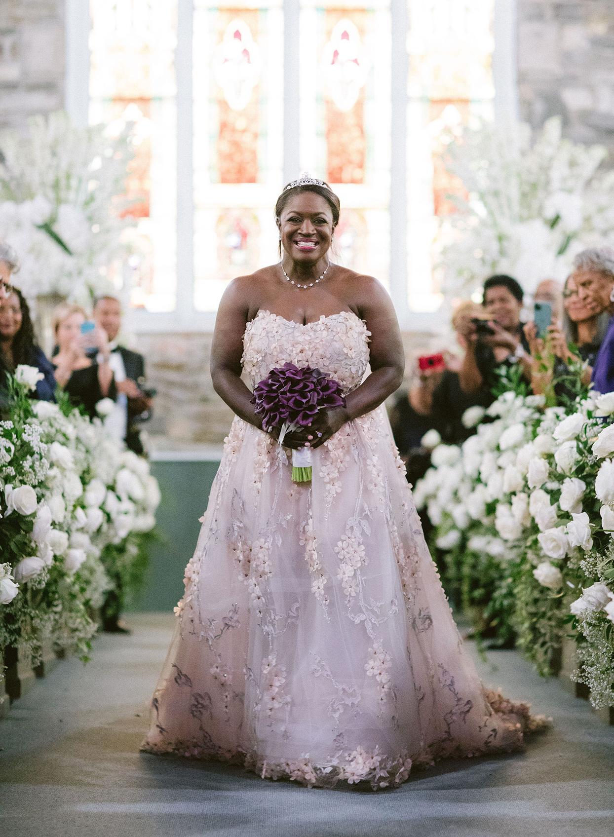 bride walking down aisle in pastel pink and purple floral wedding dress