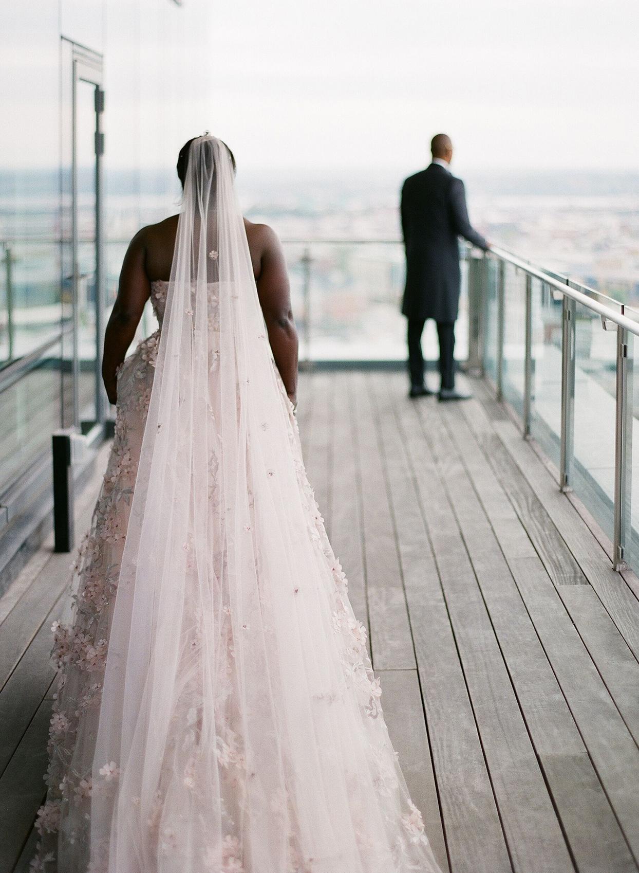 bride walking toward groom on balcony for first look