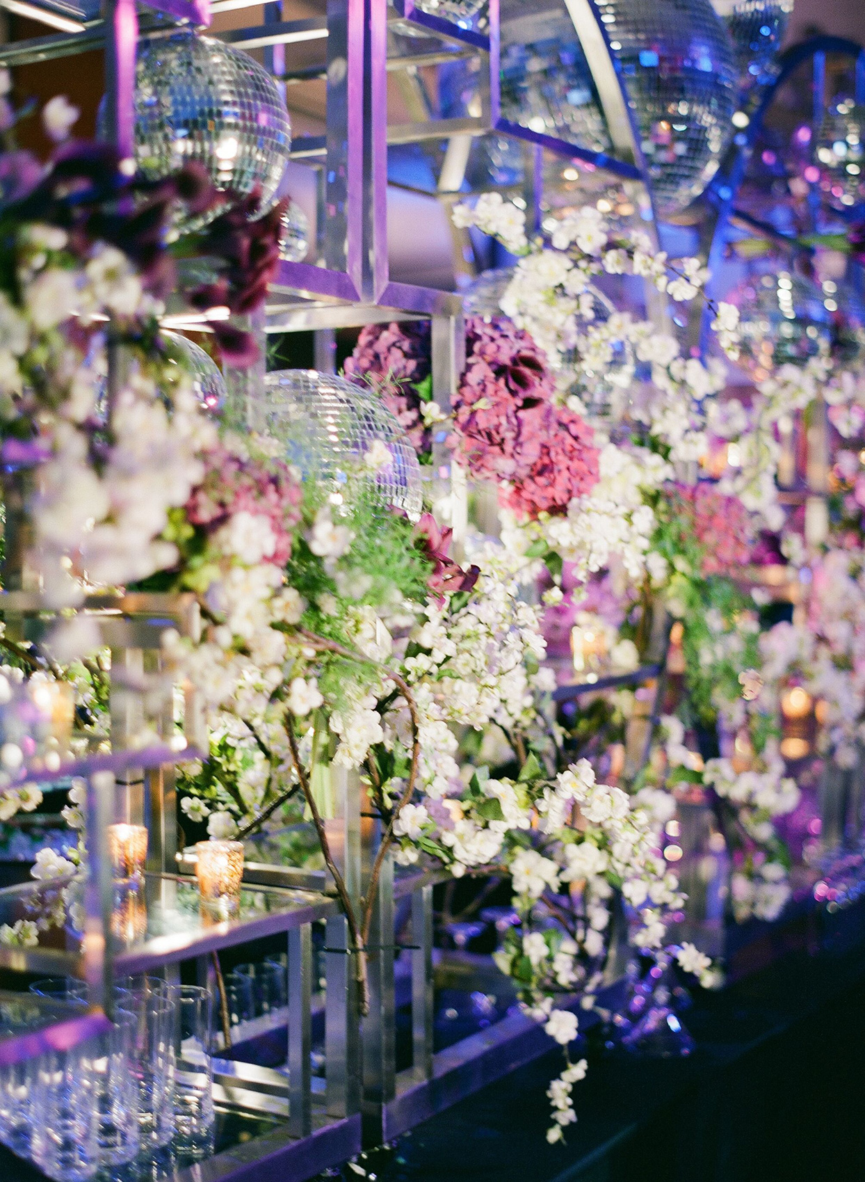 wedding bar lit with purple lights and decorated with white flowers