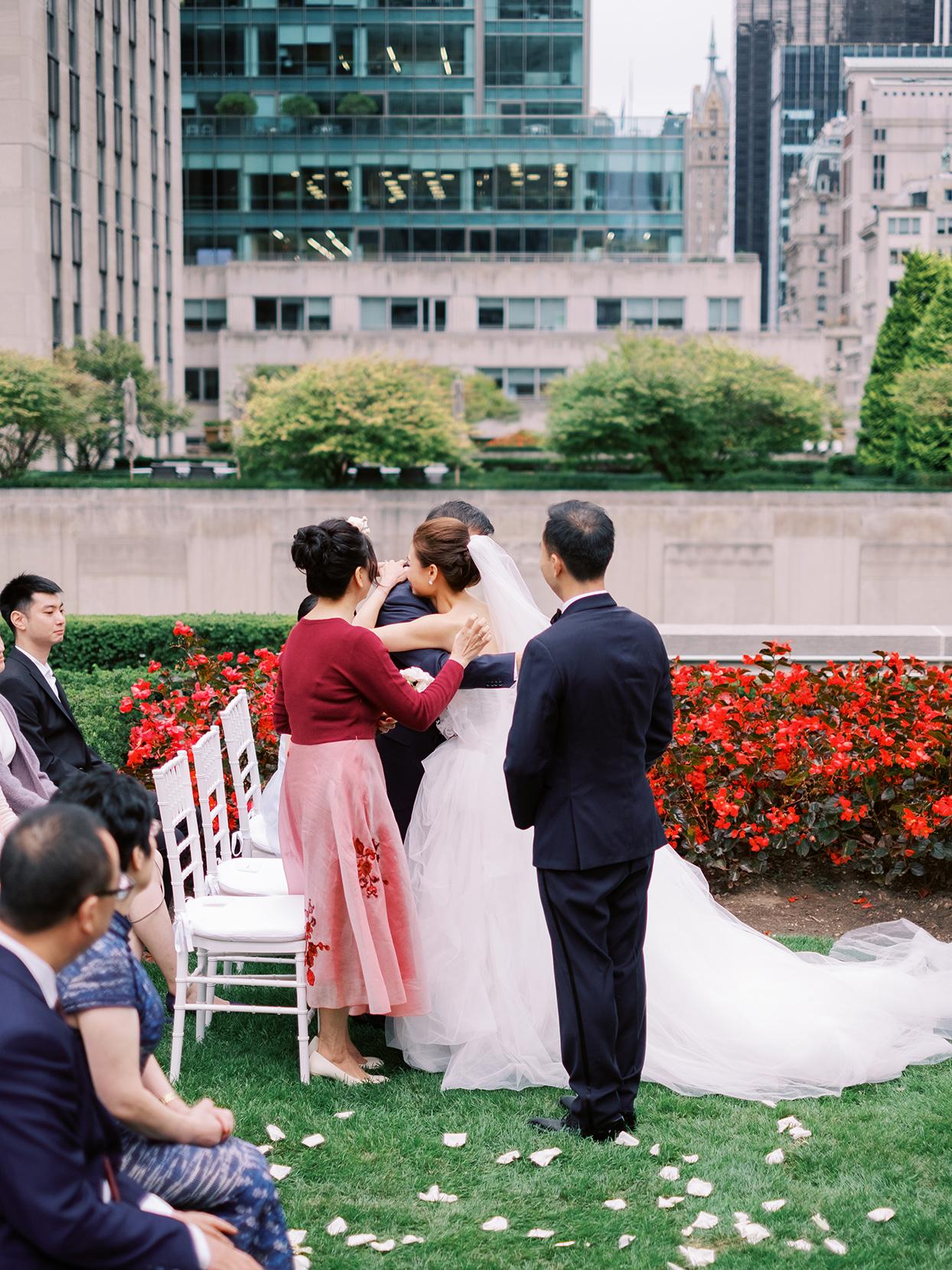 bride hugs family during wedding ceremony