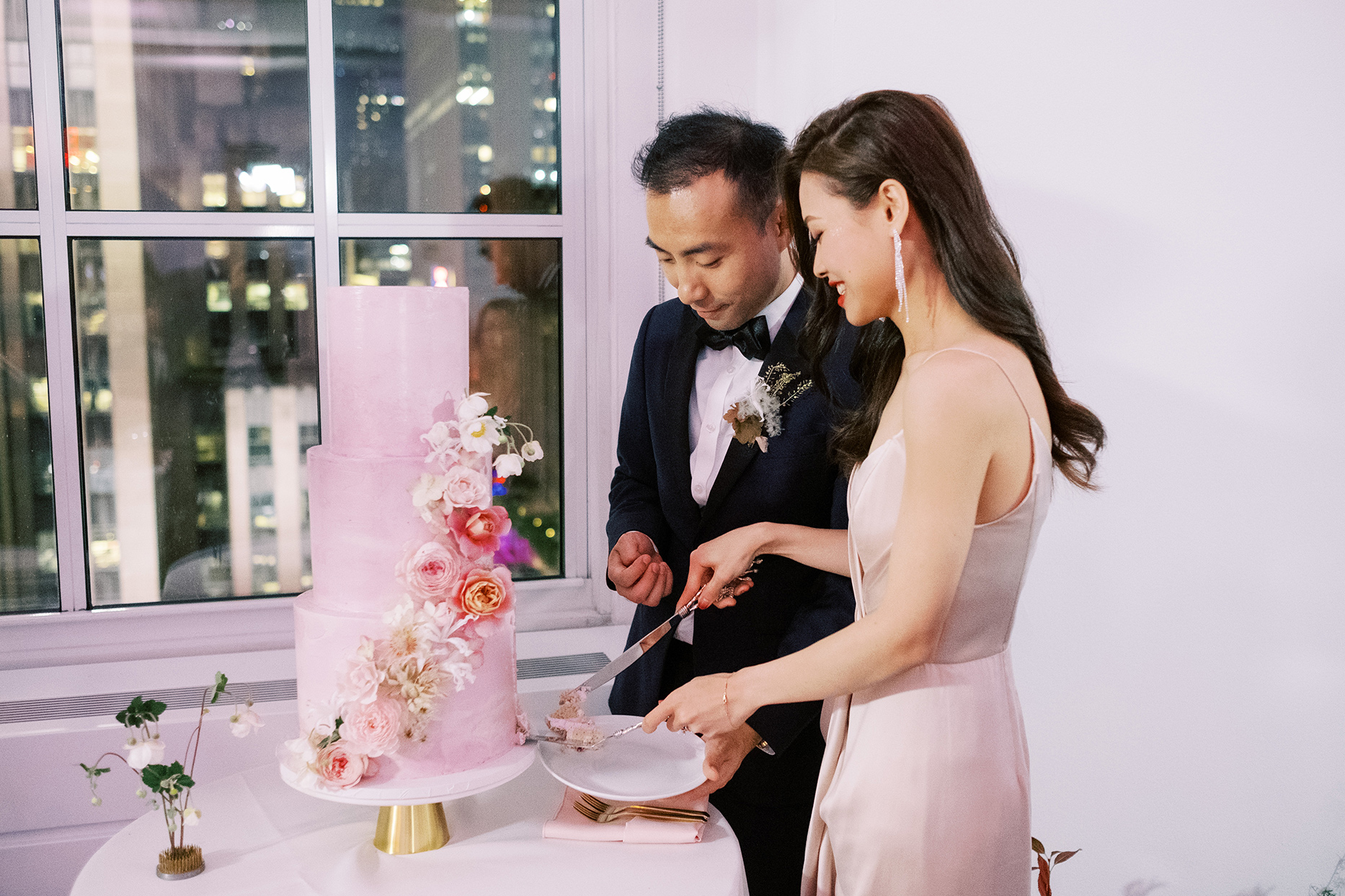 wedding couple cutting pastel pink cake