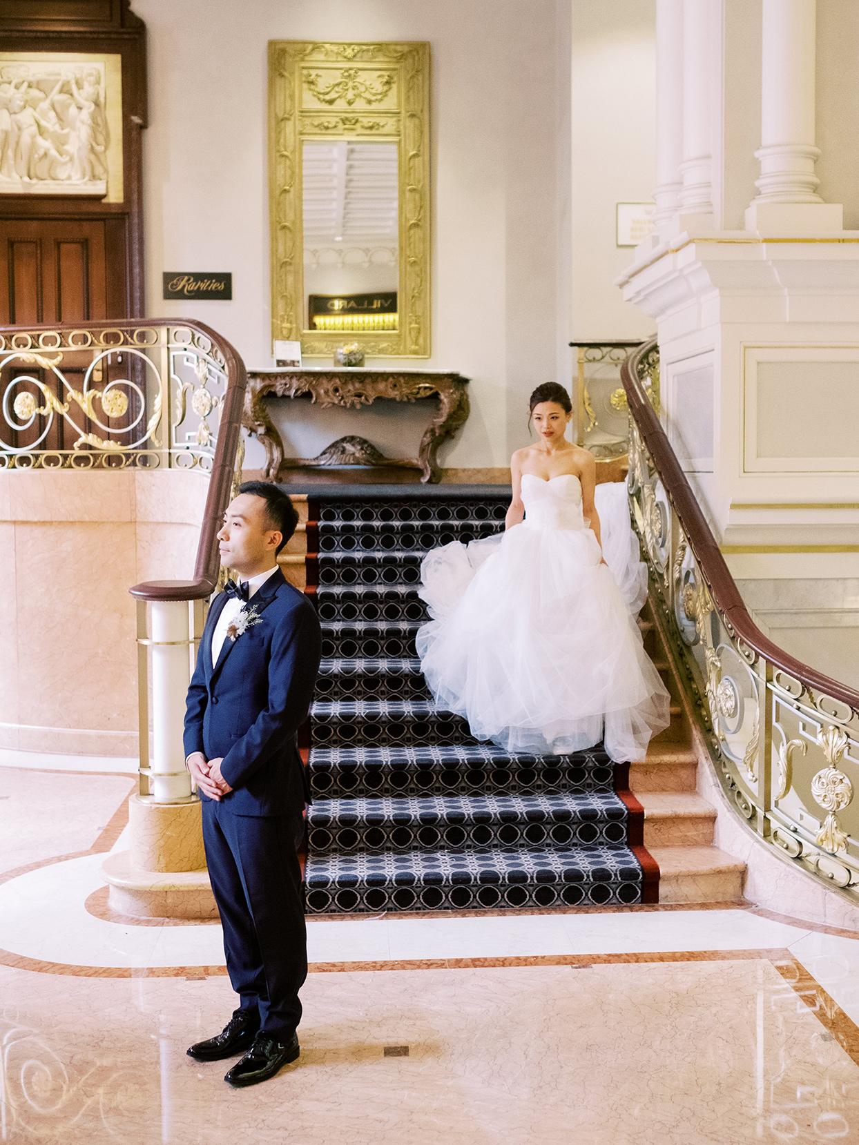 bride walking down stairs toward groom for first look