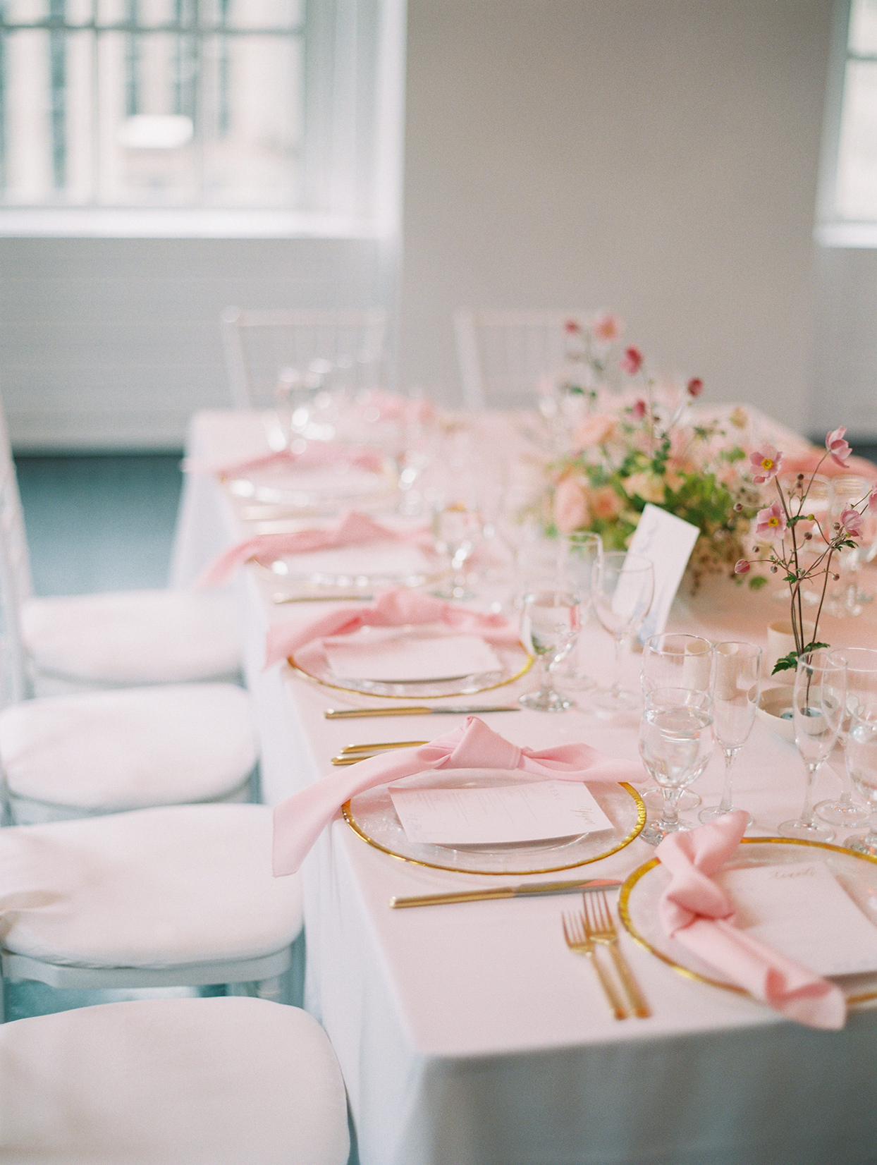 pastel pink and gold wedding place settings at long tables