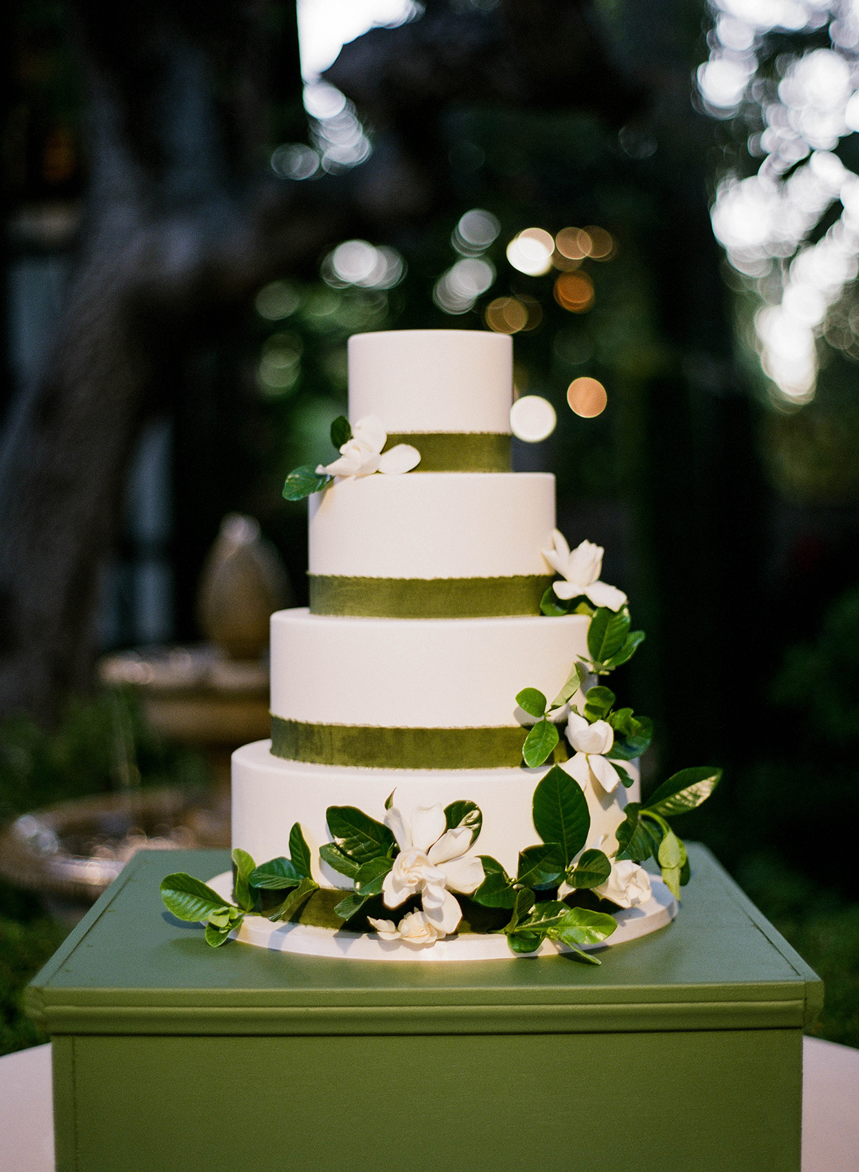 four tiered white wedding cake with green ribbons and flowers