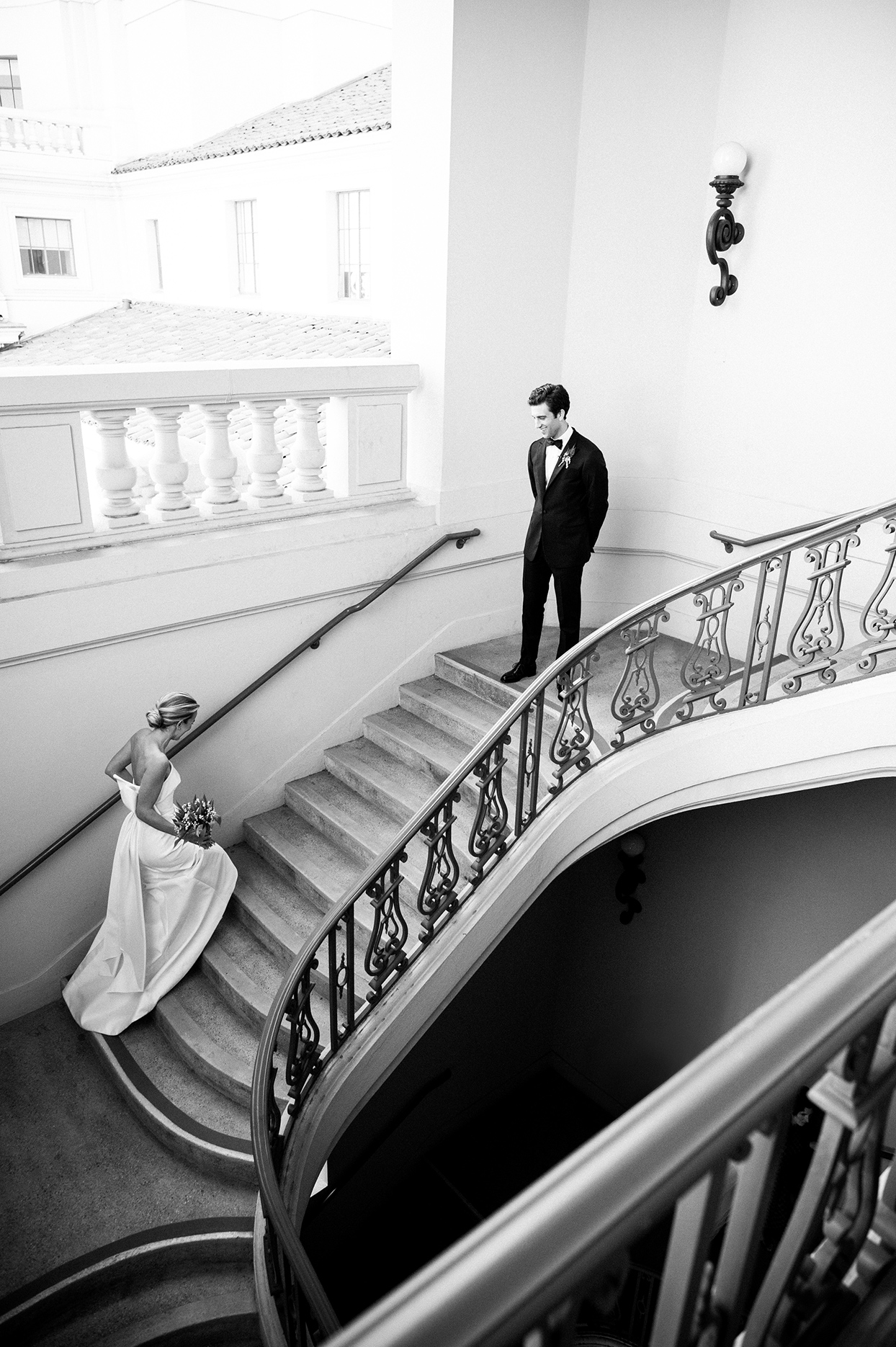 bride walking up courthouse stairs toward groom for first look