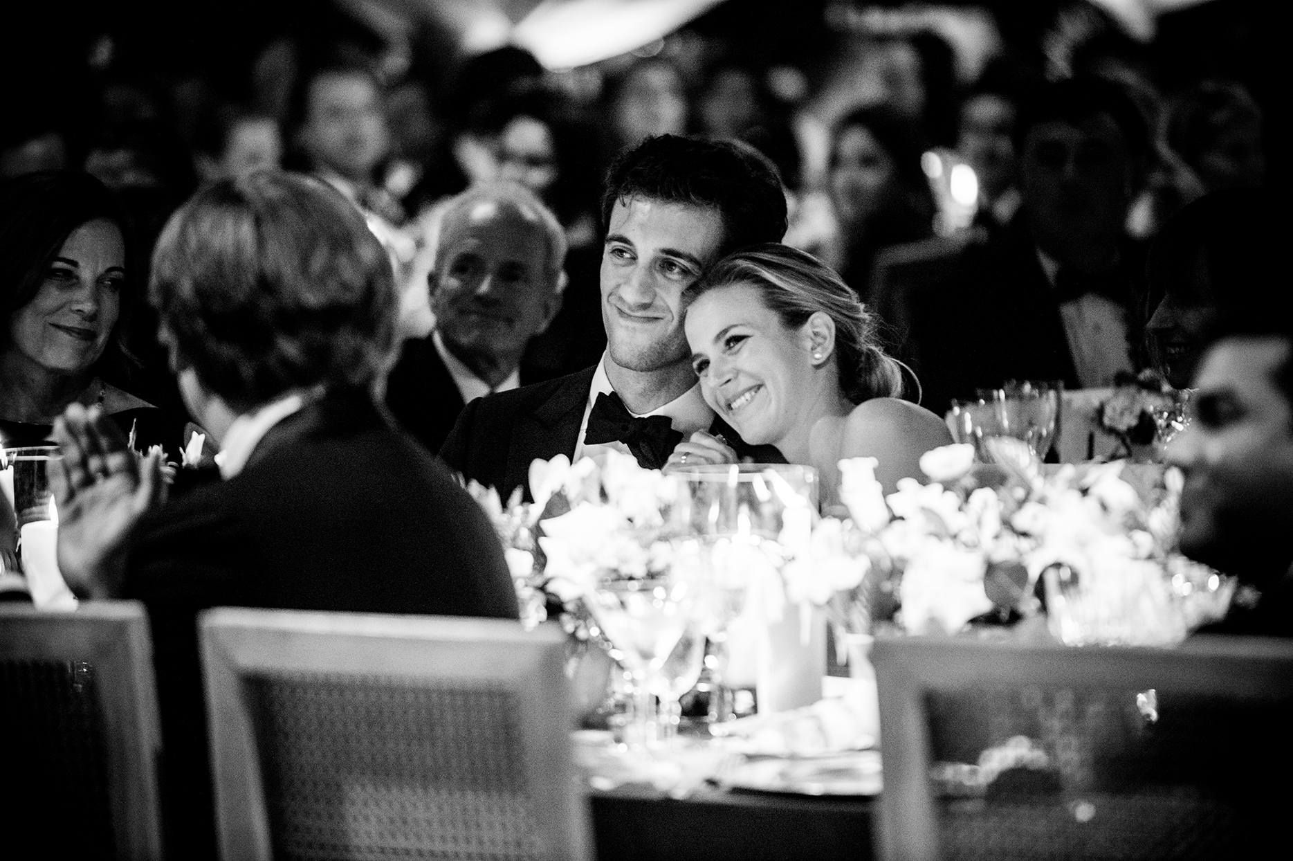 bride and groom sitting together during reception speeches