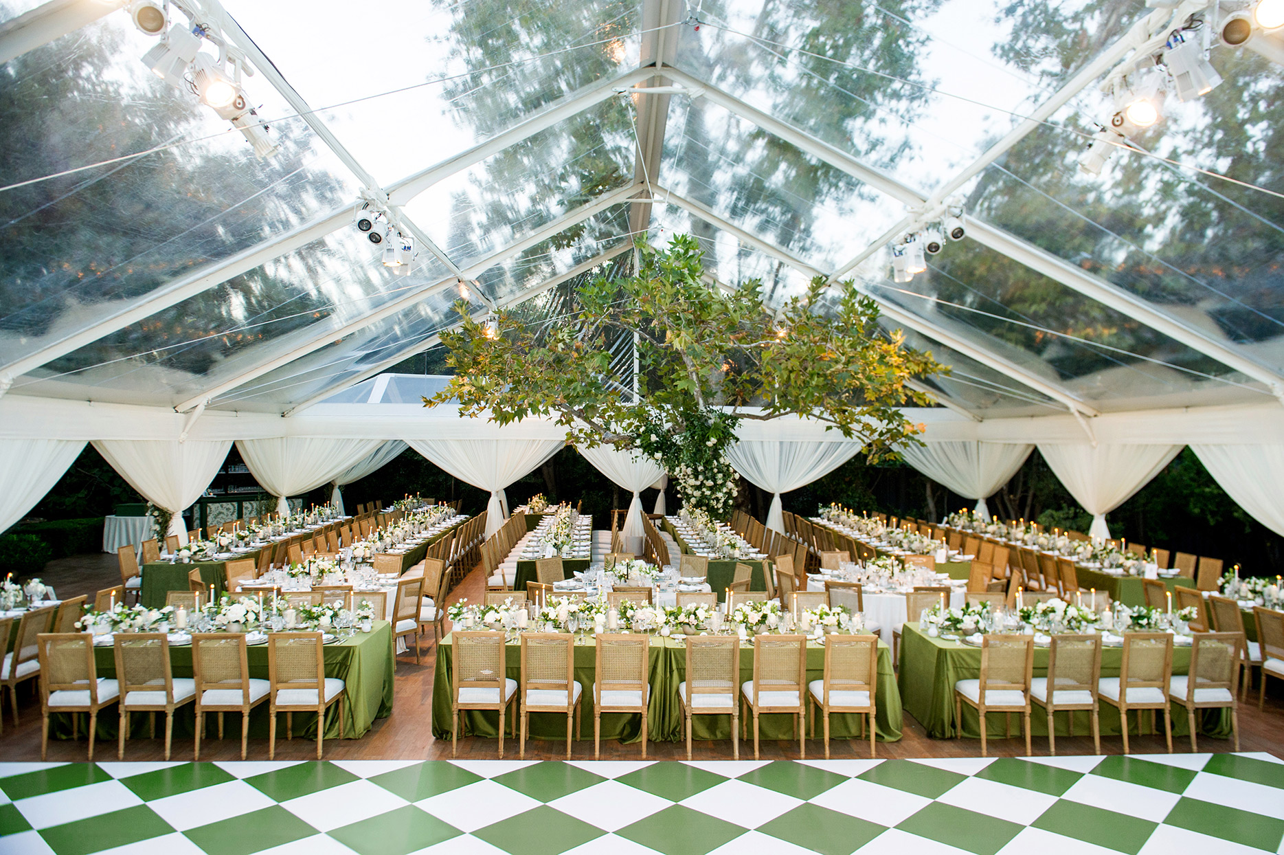 wedding transparent tent with white and green tables set up inside