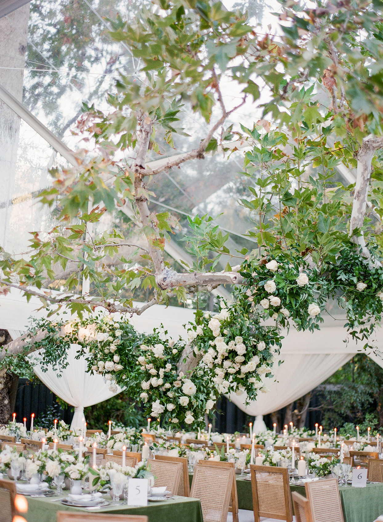 floral garland hanging on tree inside reception tent