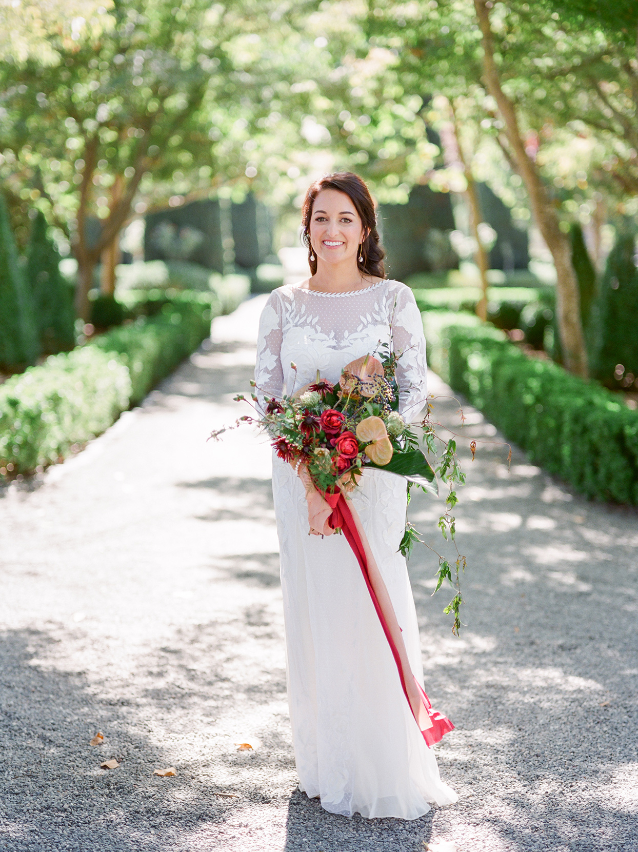 bride holding red and orange fall bouquet standing on gravel road