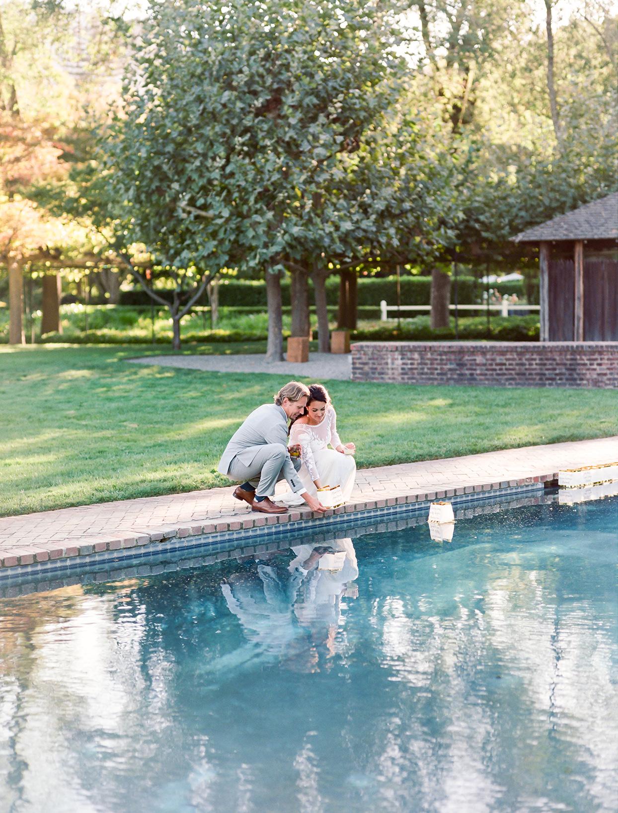 bride and groom releasing floating lantern in swimming pool
