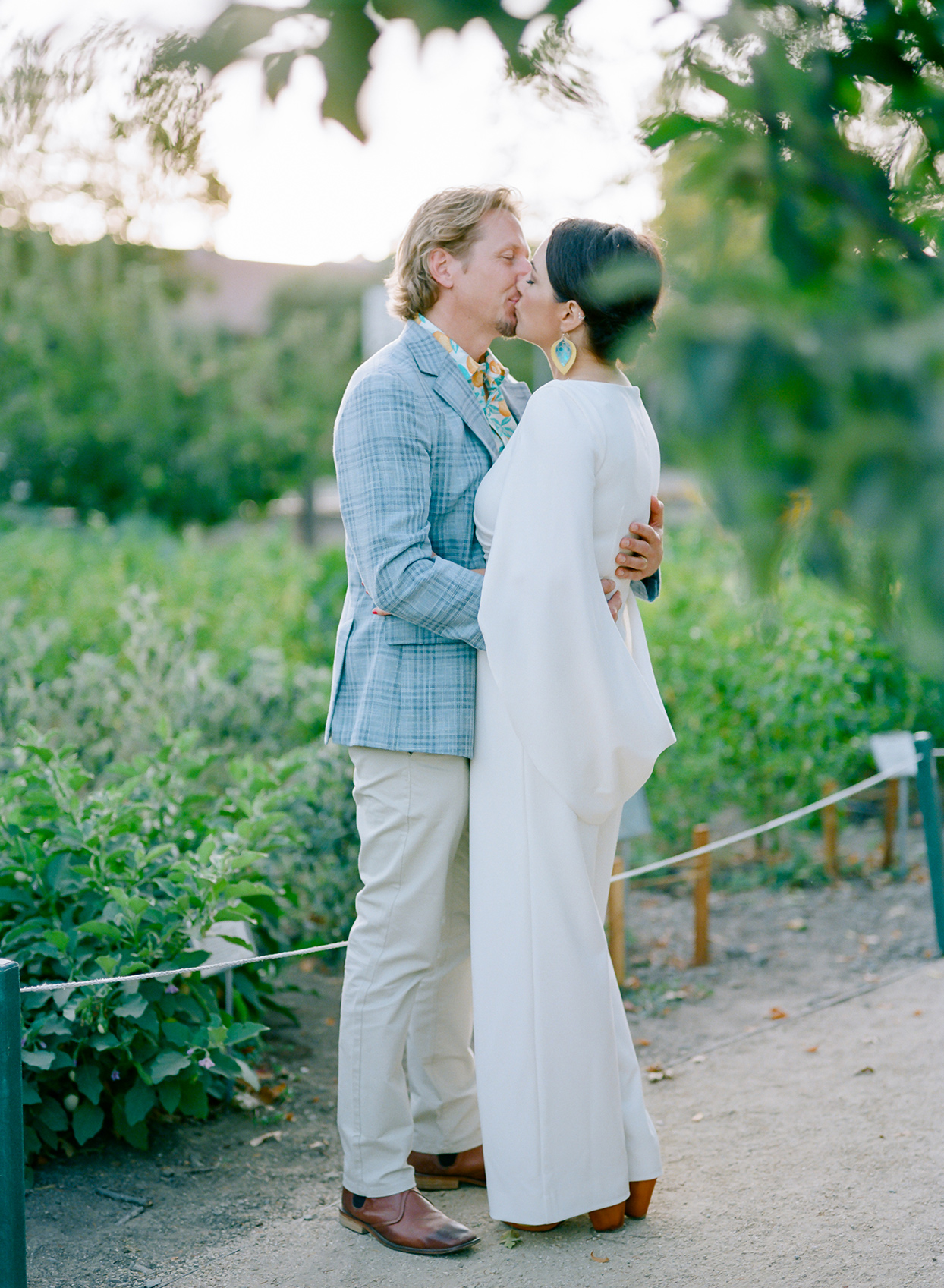 couple kissing in casual attire by garden