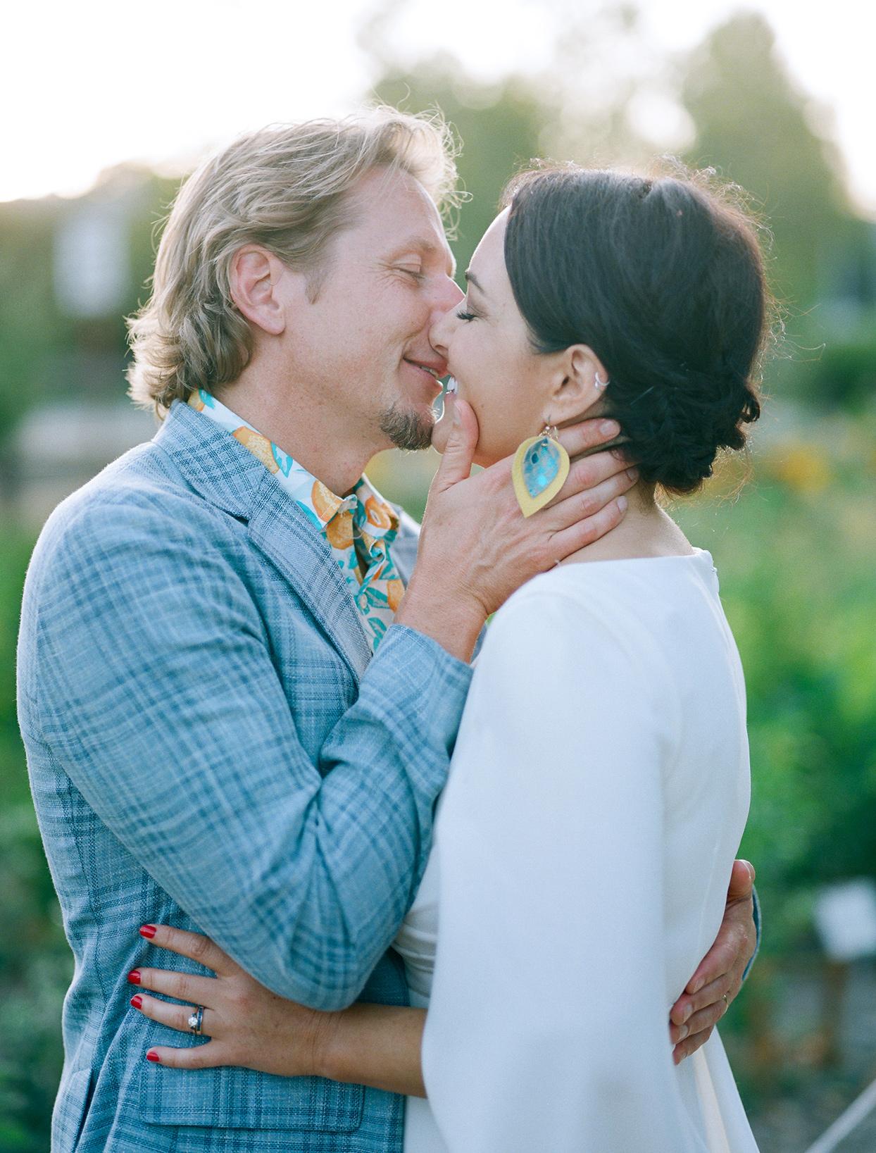 couple kissing in casual reception attire