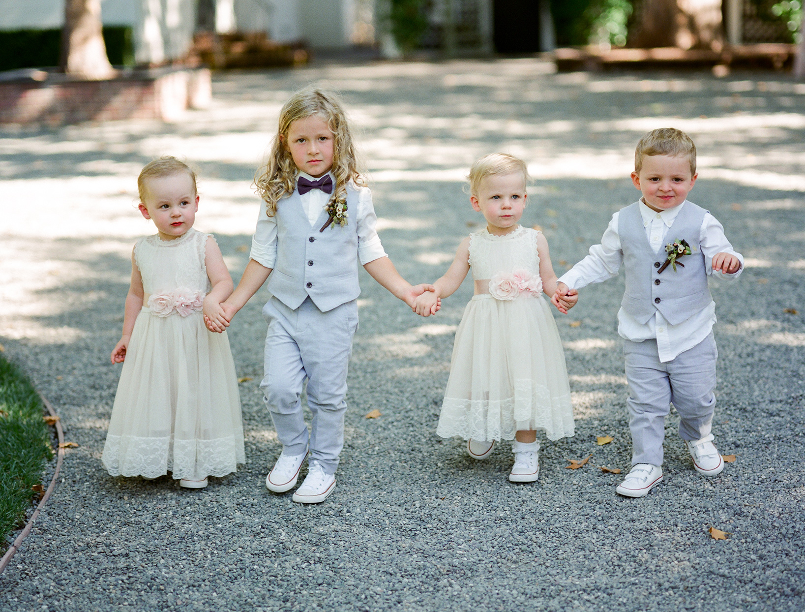 flower girls and ring bearers walking together down gravel road