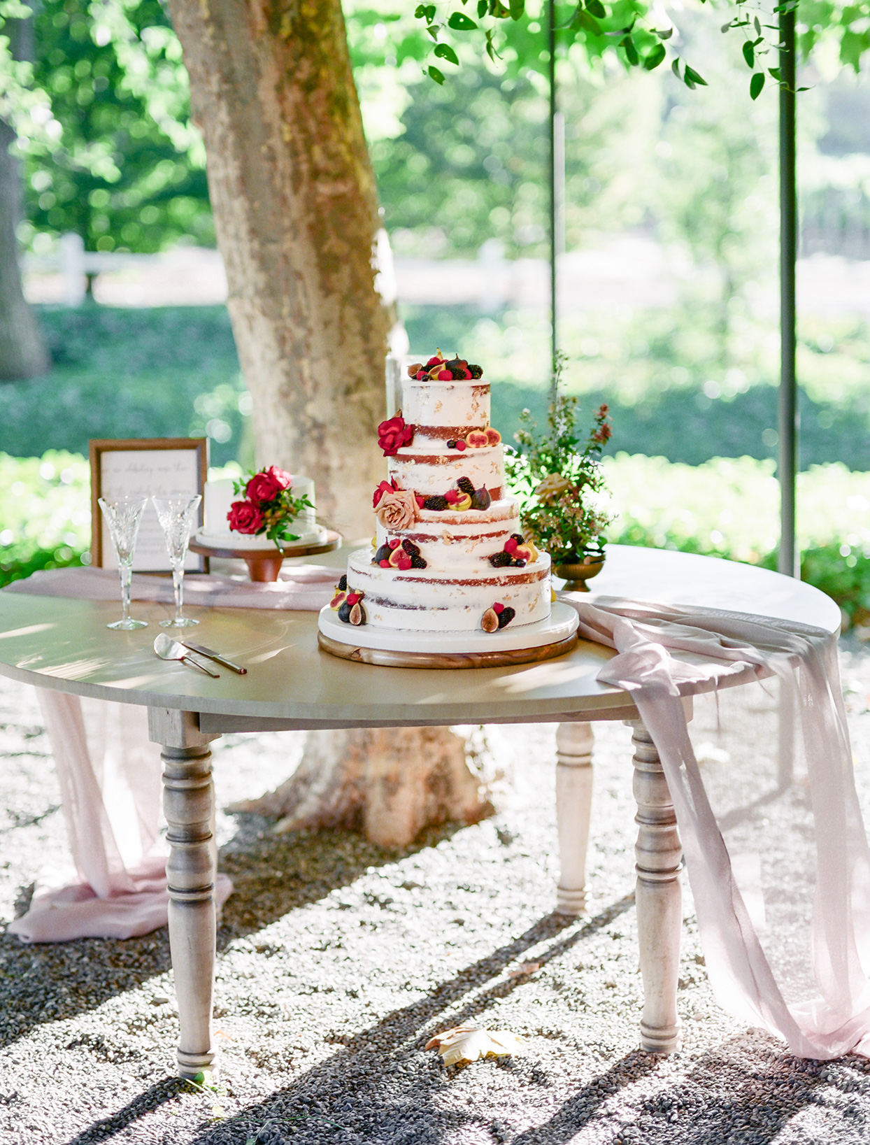 partially naked wedding cake with fruit and floral decorations
