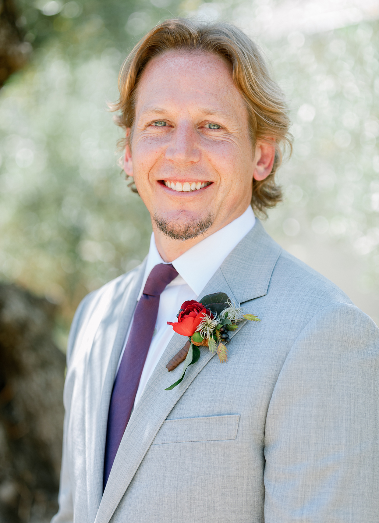 groom in light gray suit with fall boutonniere