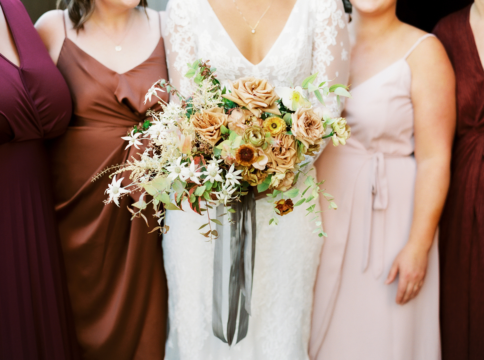 bride holding fall colored wedding bouquet with bridesmaids