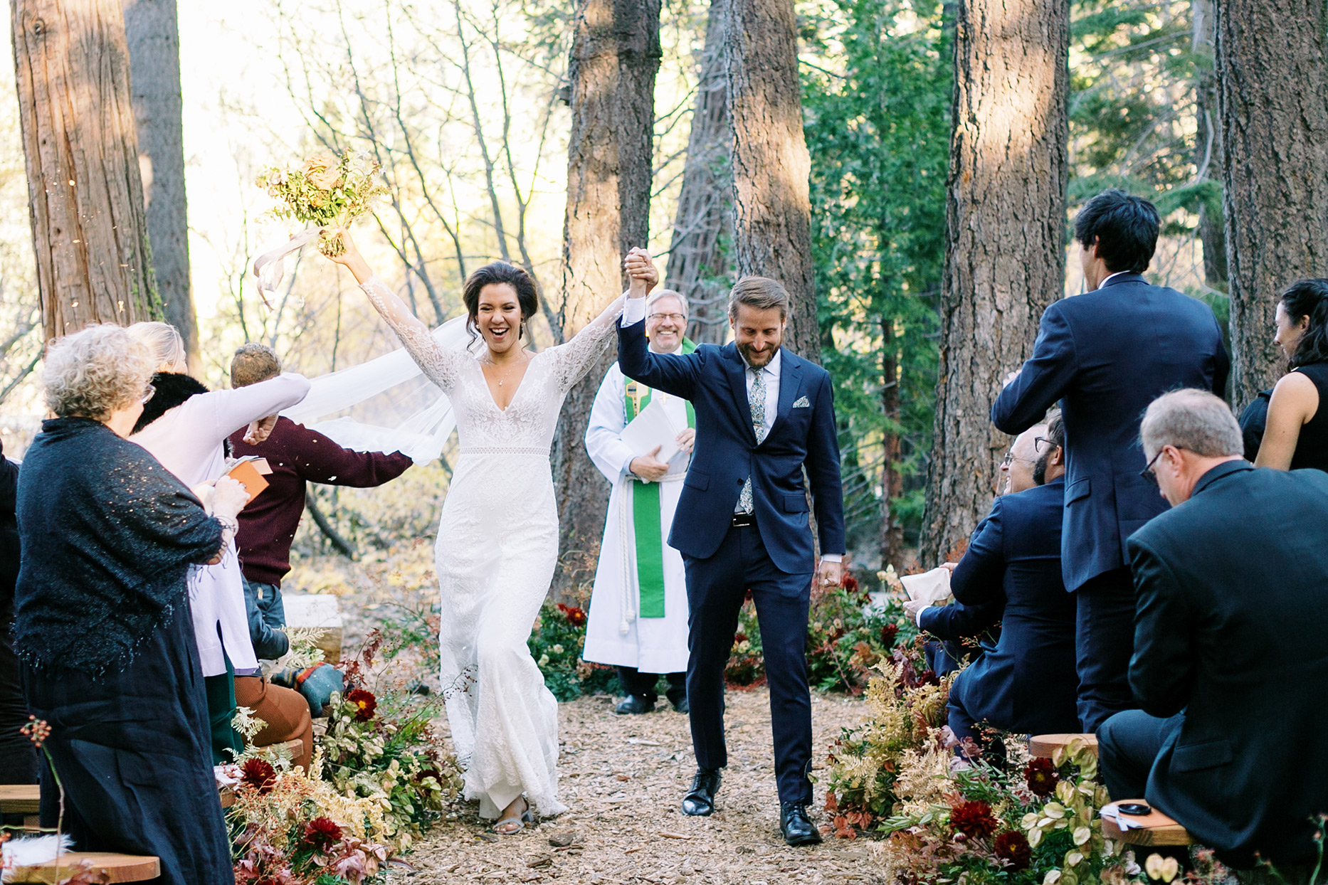 couple raising hands in excitement as they are announced at ceremony