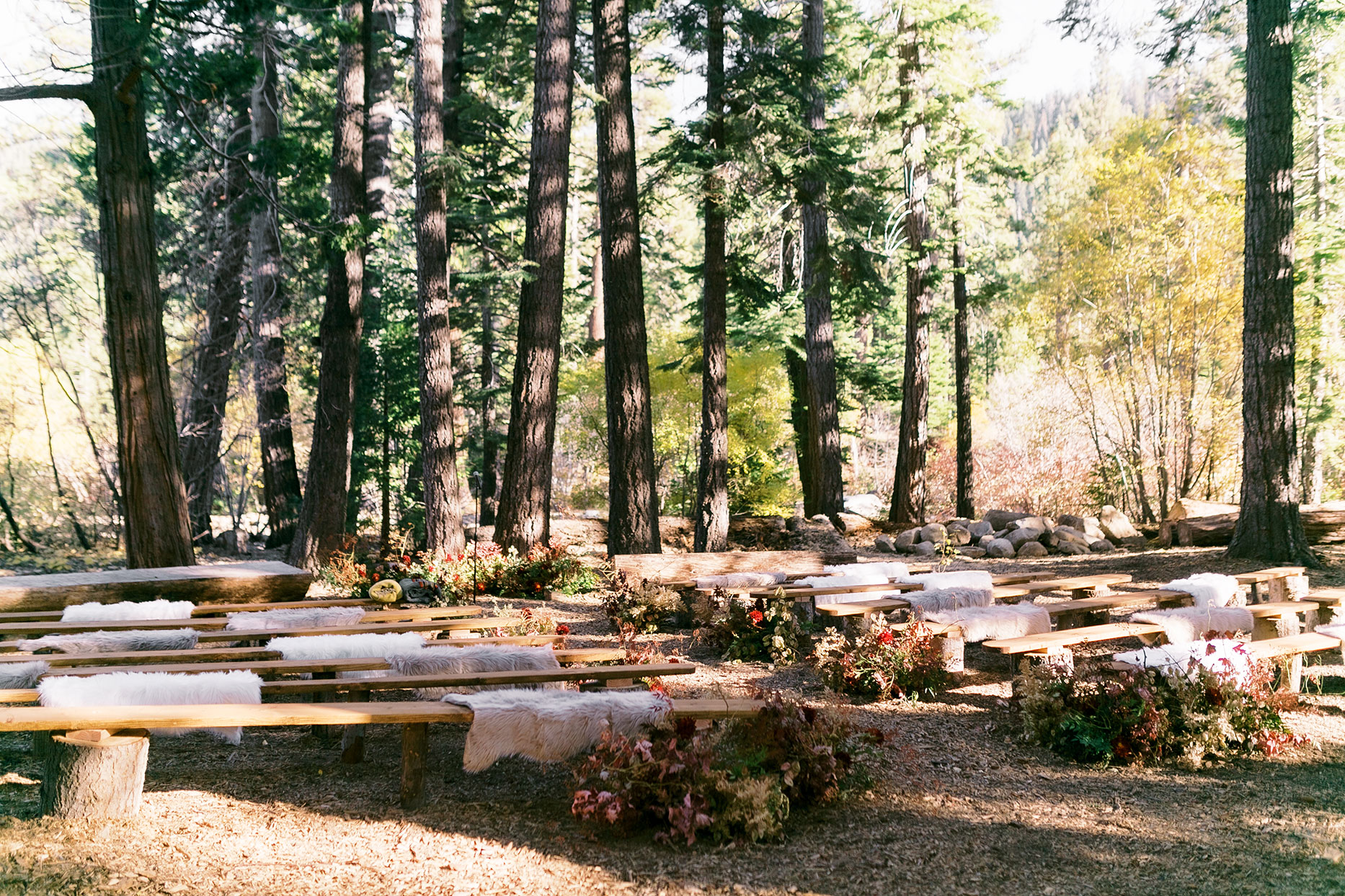 rustic outdoor ceremony space with wooden benches