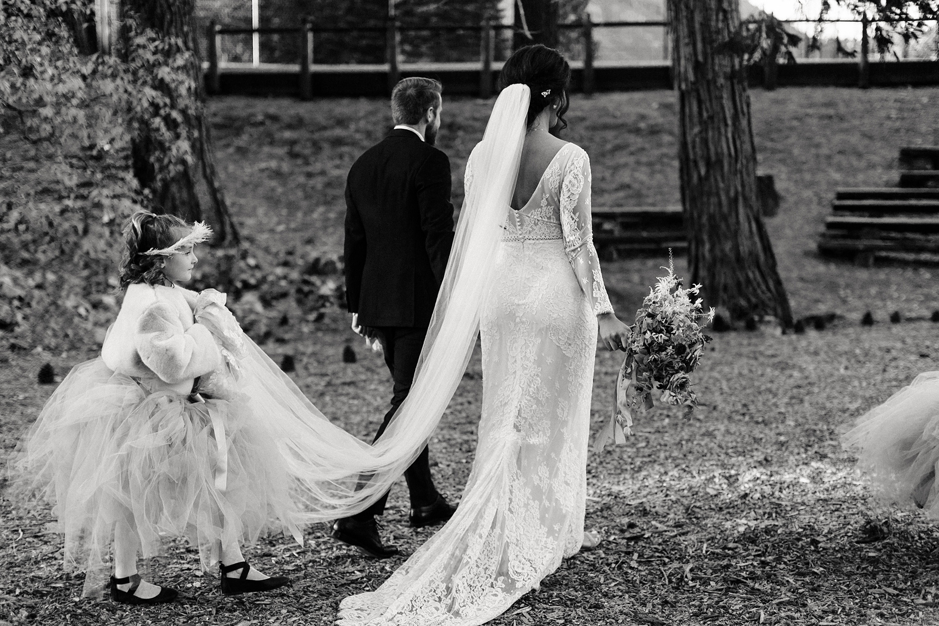 wedding couple walking together while flower girl carries veil train