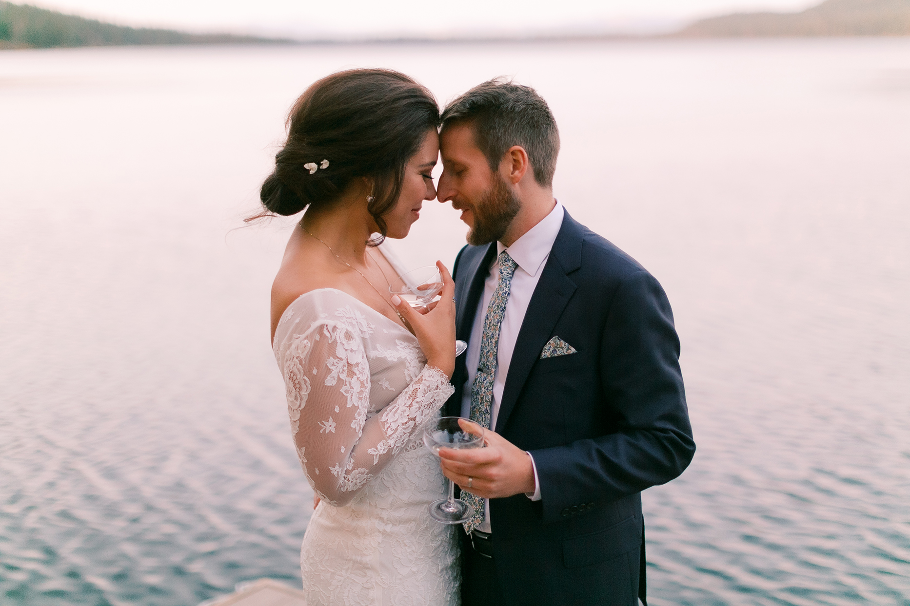 wedding couple embracing while holding champagne glasses by lake