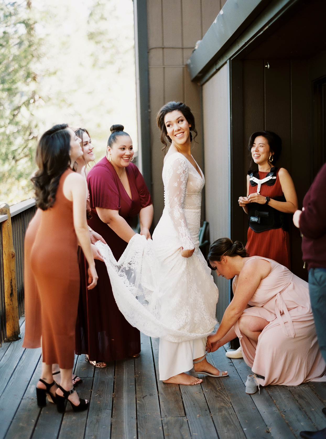 bride getting ready with bridesmaids in fall colors
