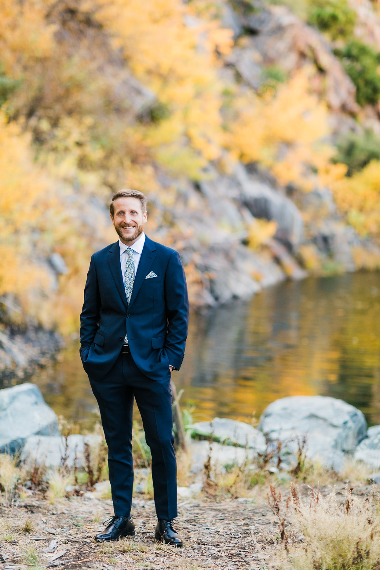 groom in dark blue suit standing by water and fall foliage
