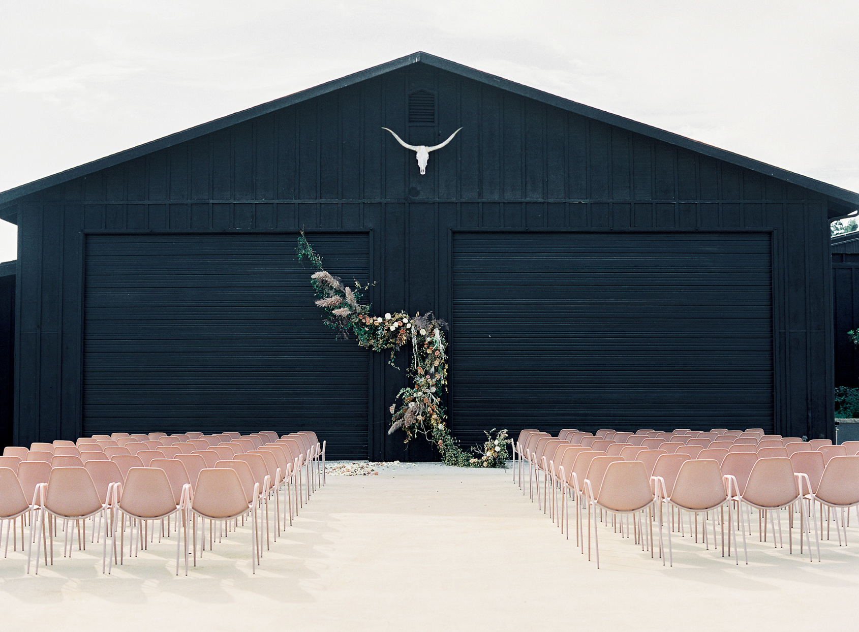 wedding ceremony set up with blush chairs in front of black barn