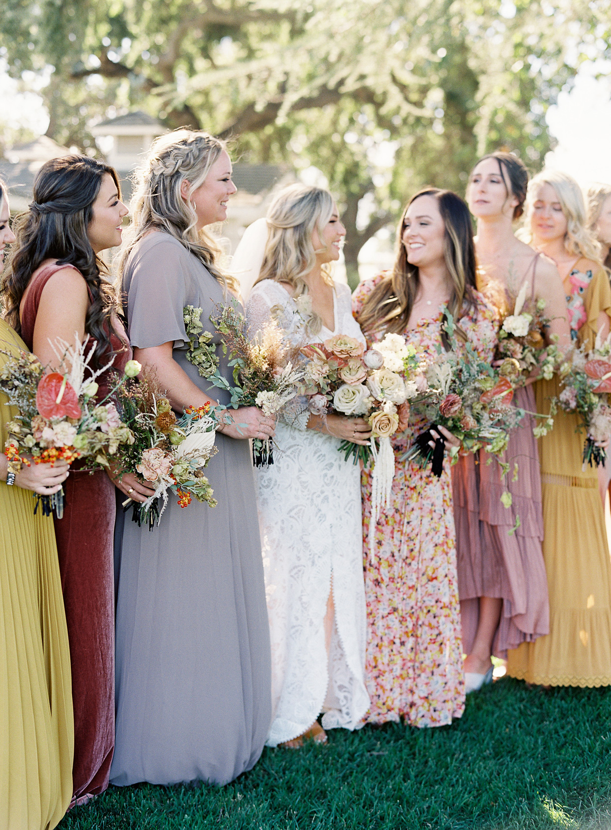 bride posing with bridesmaids in mismatched dresses