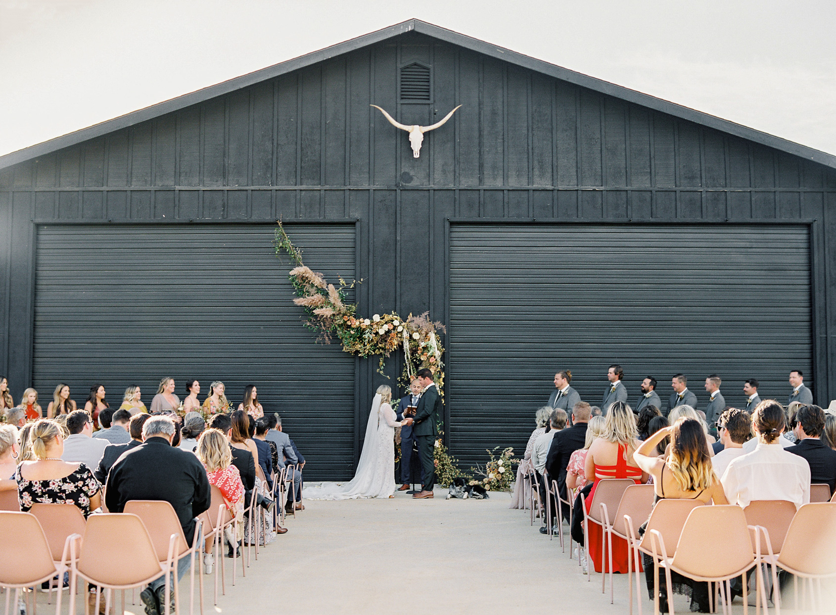 wedding ceremony in front of black barn