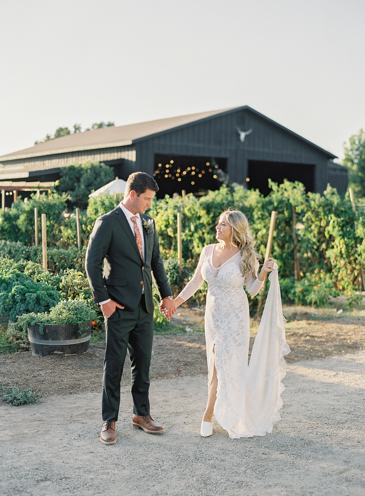 bride and groom holding hands in front of farm field