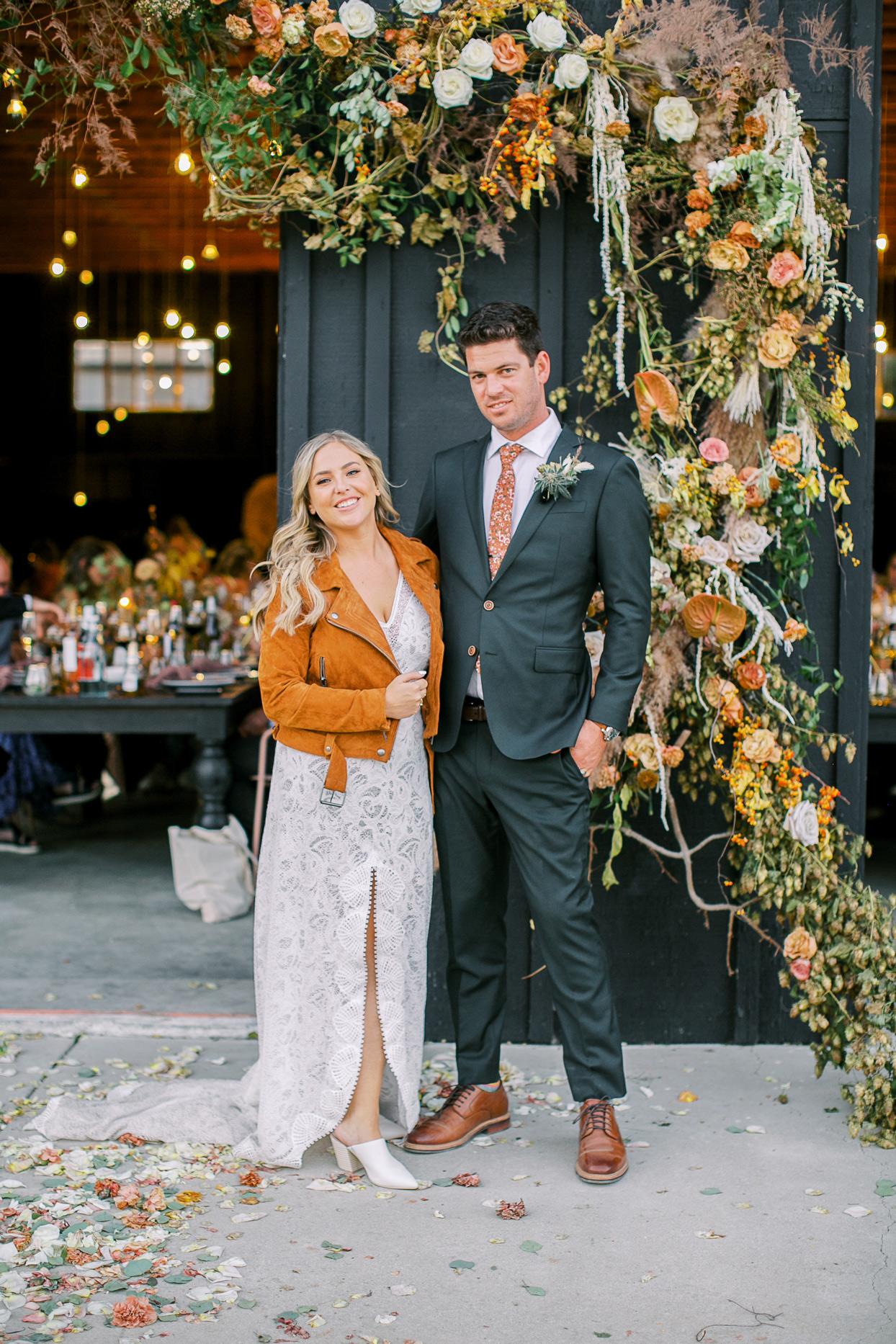 bride and groom posing in front of barn door